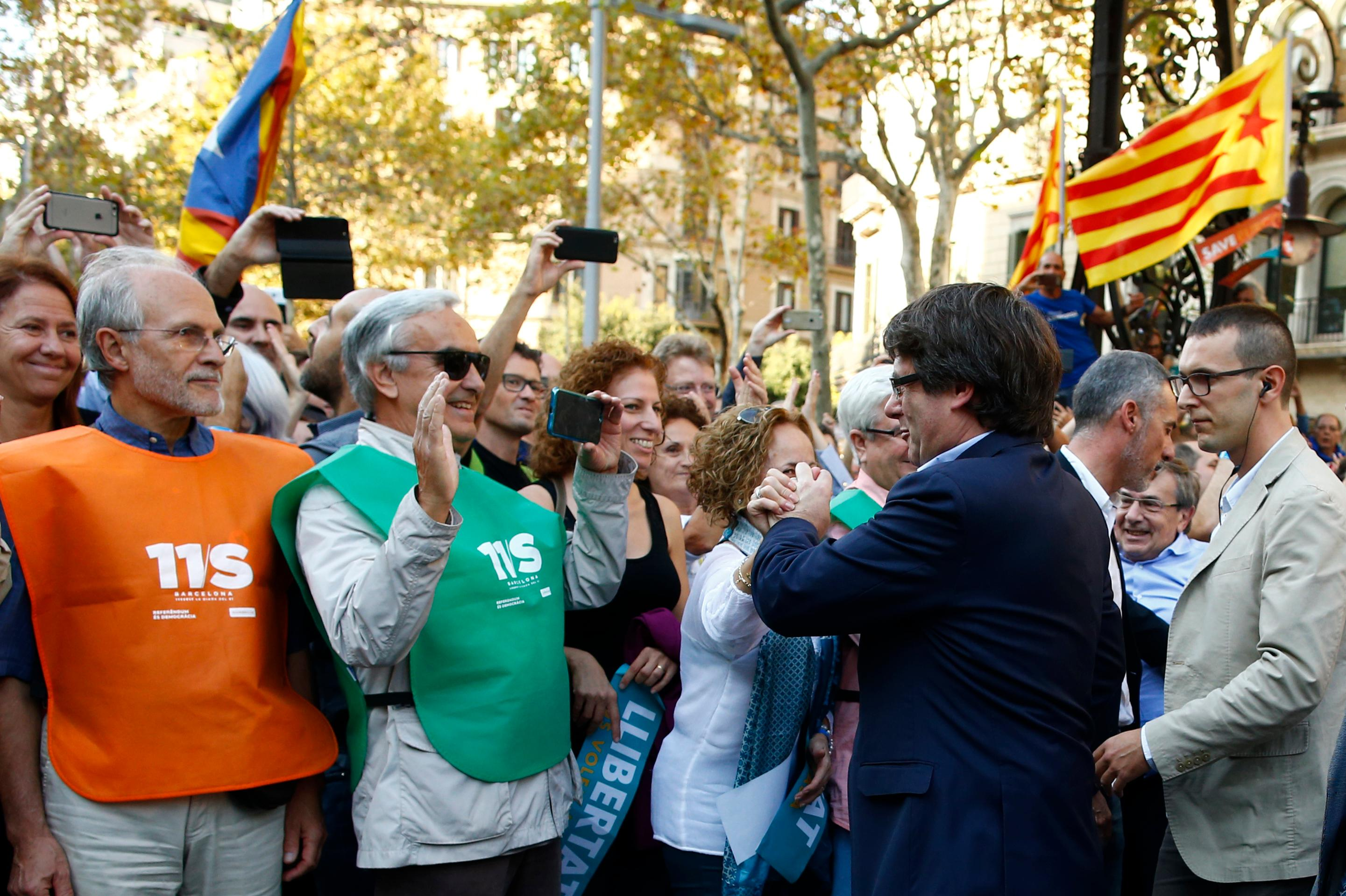 Catalan President Carles Puigdemont greets protesters before the start of a march to protest against the National Court's decision to imprison civil society leaders, in Barcelona, Spain, Saturday, Oct. 21, 2017. The Spanish government moved decisively Saturday to use a previously untapped constitutional power so it can take control of Catalonia and derail the independence movement led by separatist politicians in the prosperous industrial region. AP Photo/Manu Fernandez)