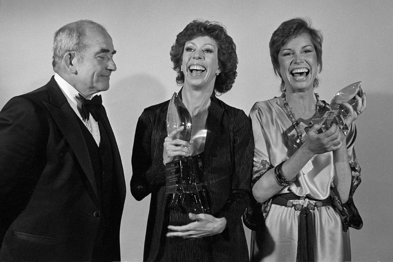 Carol Burnett, center, and Mary Tyler Moore, right, who both tied for the Favorite Female TV Performer award, accept their People's Choice Awards from actor Ed Asner, in Los Angeles, Calif., March 7, 1979. (AP Photo/Reed Saxon)