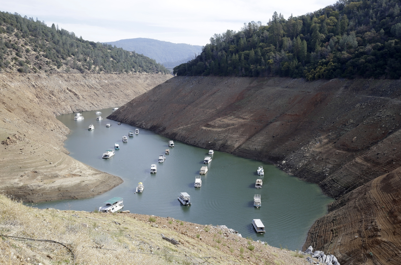 FILE - In this Thursday, Oct. 30, 2014 file photo, houseboats sit in the drought lowered waters of Oroville Lake, near Oroville, Calif.  More than 40 percent of California has emerged from a punishing drought that covered the whole state a year ago, federal drought-watchers said Thursday, Jan. 12, 2017  a stunning transformation caused by an unrelenting series of storms in the North that filled lakes, overflowed rivers and buried mountains in snow. (AP Photo/Rich Pedroncelli, File)