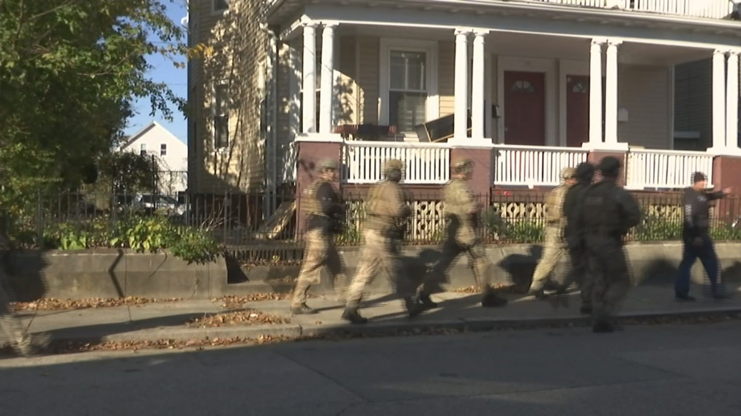 Police officers in tactical gear search a Providence neighborhood where a stolen state police cruiser was abandoned, Thursday, Nov. 9, 2017. (WJAR)<p></p>