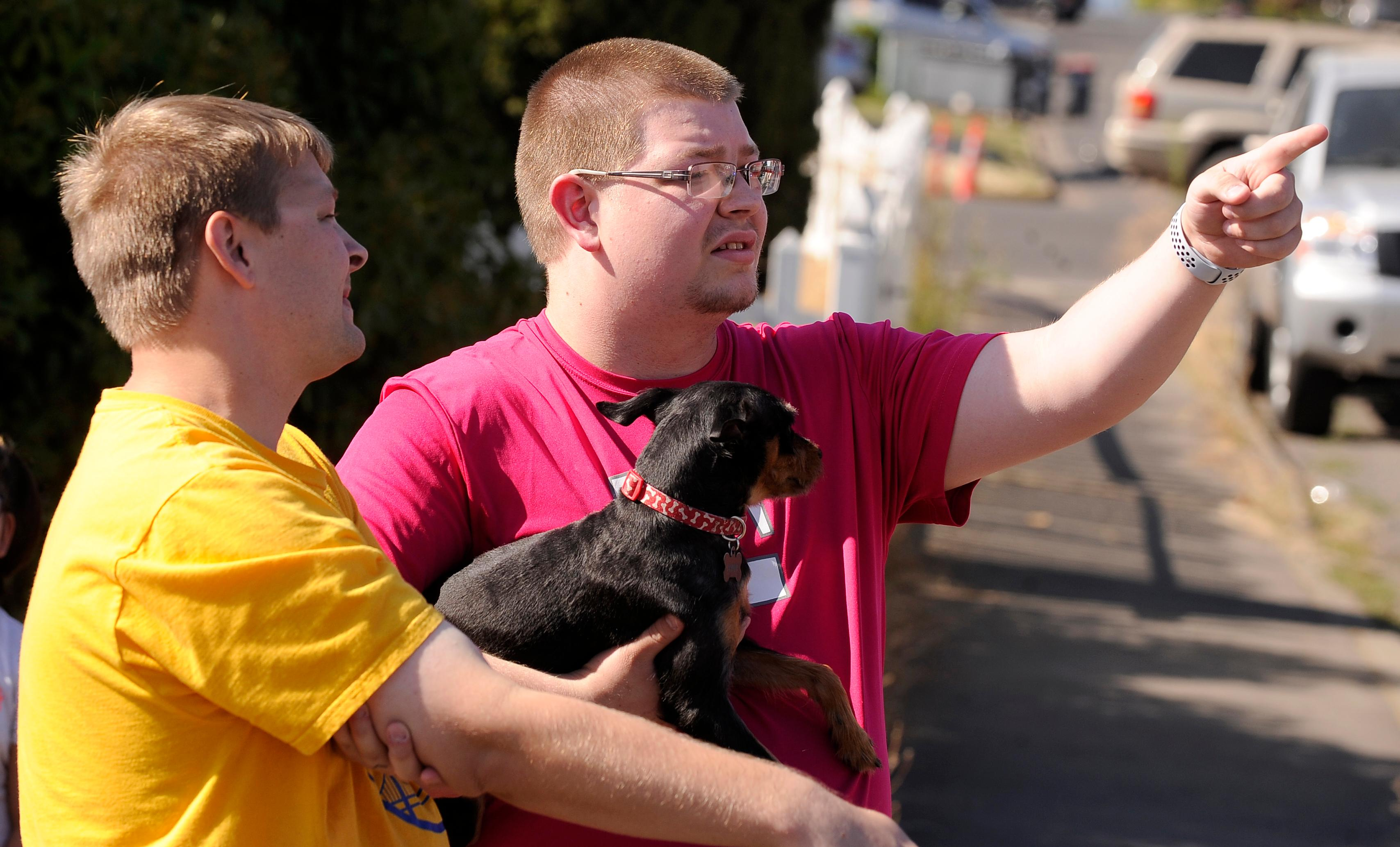 Andy Atkinson / Mail TribuneTimothy and Justin Huckabee with their dog Scout watch firefighters control a fire they escaped from that started in an apartment building on Ninth street in Central Point.