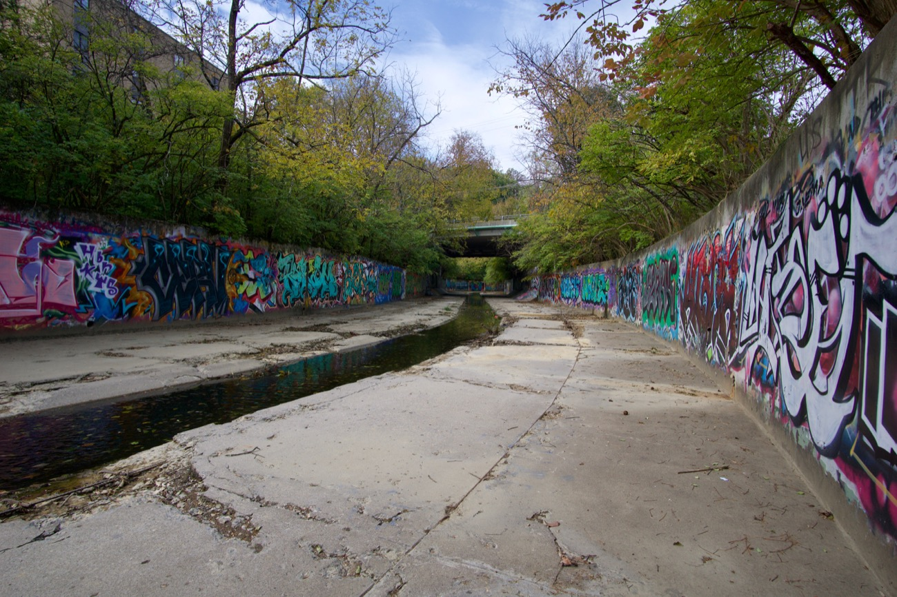 No place in Cincinnati is as secluded or spectacular as Duck Creek in Oakley. Once a robust, natural artery connecting the Norwood flood plain to the Little Miami River, today the creek is an inert, flood-controlled pass-through. Its concrete retaining walls, however, are a sight to see. / Image: Brian Planalp // Published: 11.5.18