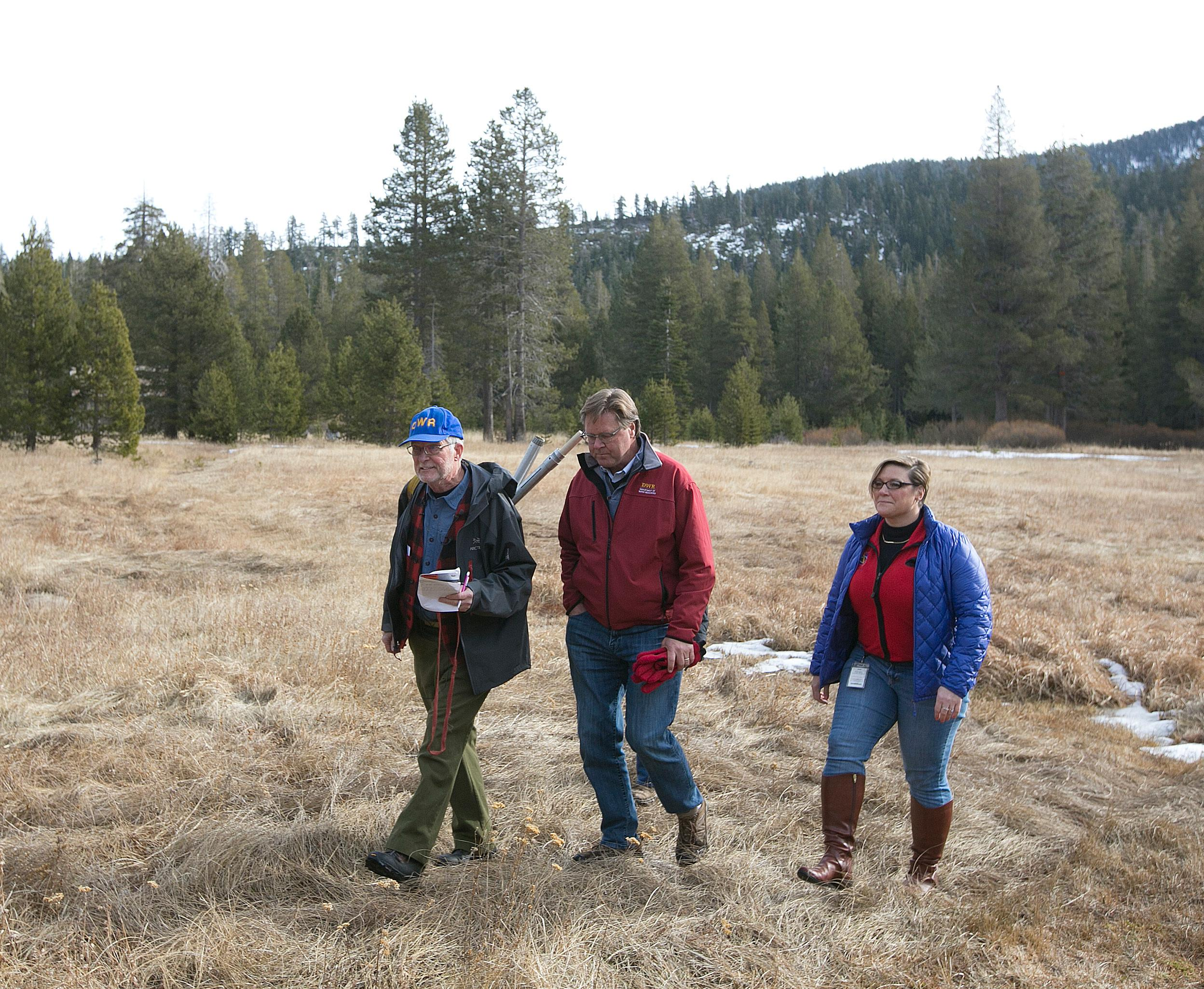 Frank Gehrke, chief of the California Cooperative Snow Surveys Program for the Department of Water Resources, left, accompanied by Grant Davis, director of the Dept. of Water Resources, center and Michelle Mead, a meteorologist with the National Weather Service, leave the nearly snow barren Phillips Station snow course, after conducting the first snow survey of the season, Wednesday, Jan. 3, 2018, near Echo Summit, Calif. The snow survey showed the snowpack at this location at 1.3 inches of depth with a water content of .4 inches. California's water managers are saying it's too early yet for fears that the state is sliding back into its historic five-year drought.(AP Photo/Rich Pedroncelli)