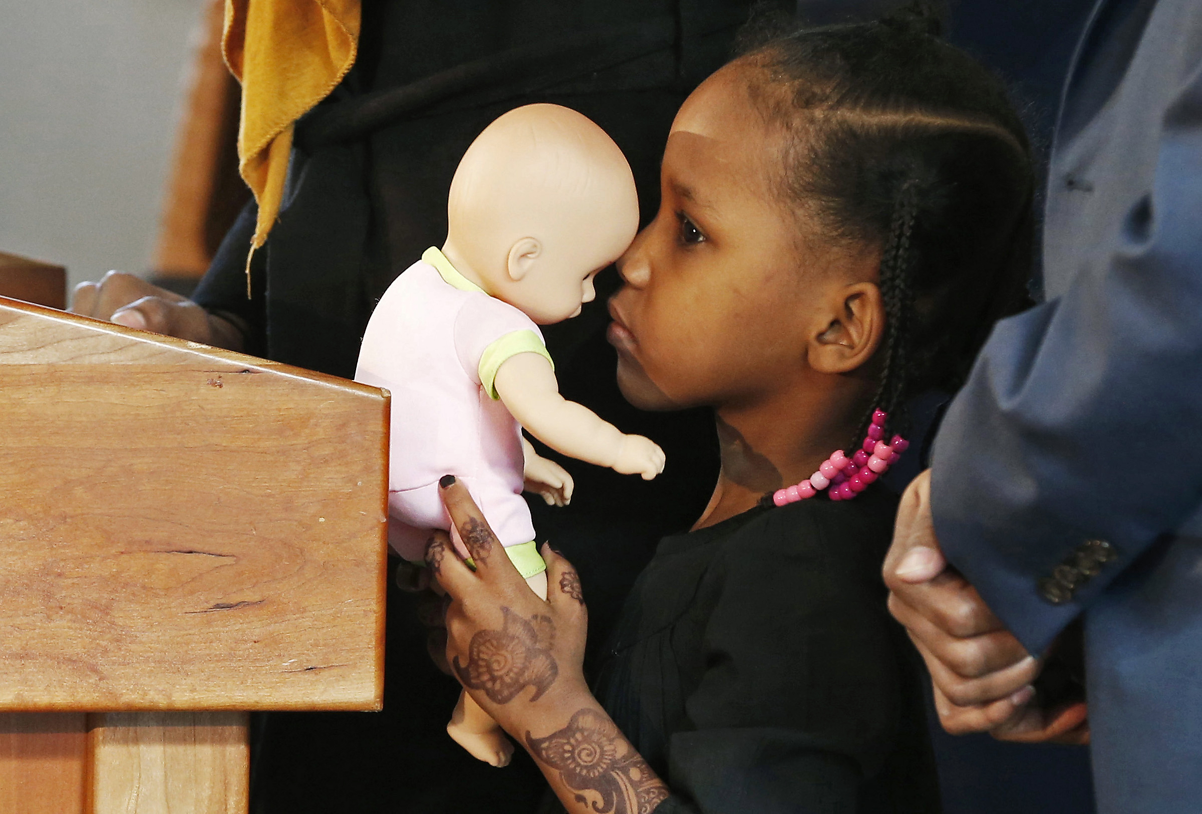 FILE - In this Feb. 3, 2017, file photo, four-year-old Somali refugee Mushkaad Abdi holds her doll as her mother, Samira Dahir, talks during a Minneapolis news conference one day after she was reunited with her family. Her trip from Uganda to Minnesota was held up by President Donald Trump's Jan. 27 order barring refugees from seven predominantly Muslim nations. A federal judge in Hawaii further weakened the already-diluted travel ban Thursday, July 13, 2017, by vastly expanding the list of U.S. family relationships that visitors from six Muslim-majority countries can use to get into the country. (AP Photo/Jim Mone, File)