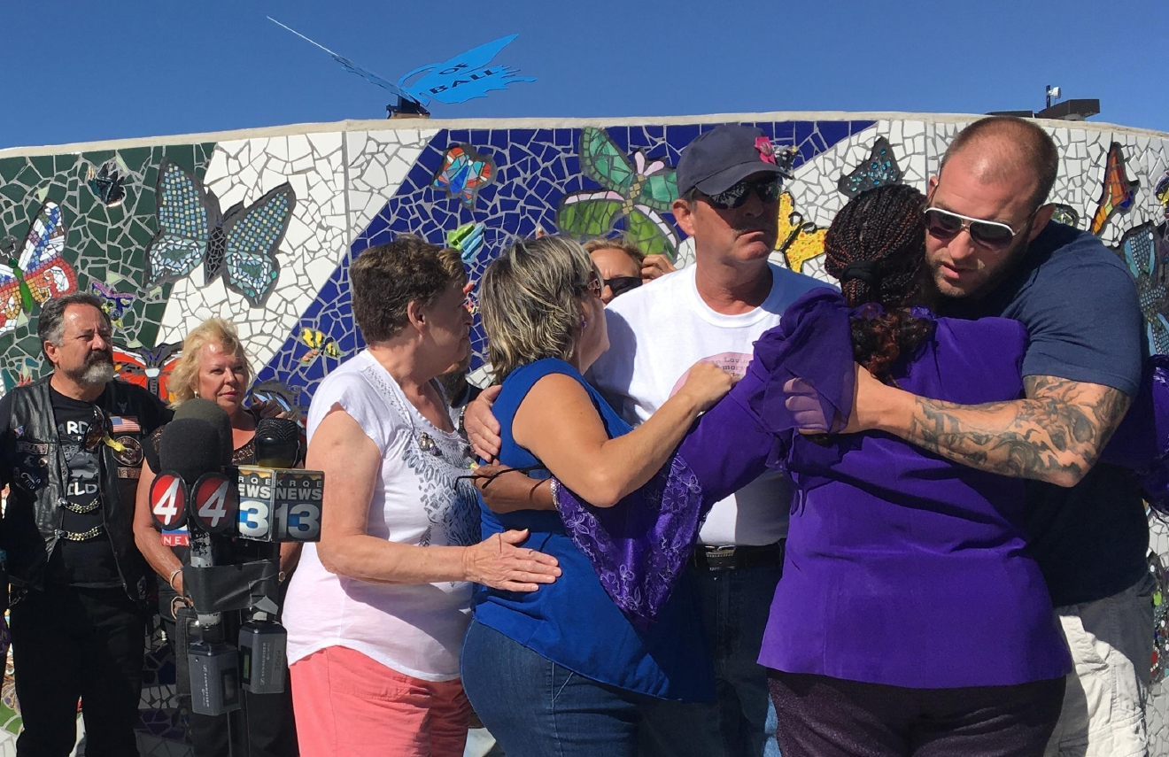 Relatives of Victoria Martens and her godmother Laura Bobbs, second from right, embrace at a children's park in Rio Rancho, New Mexico, following a news conference Monday, Aug. 29, 2016. (AP Photo/Mary Hudetz).