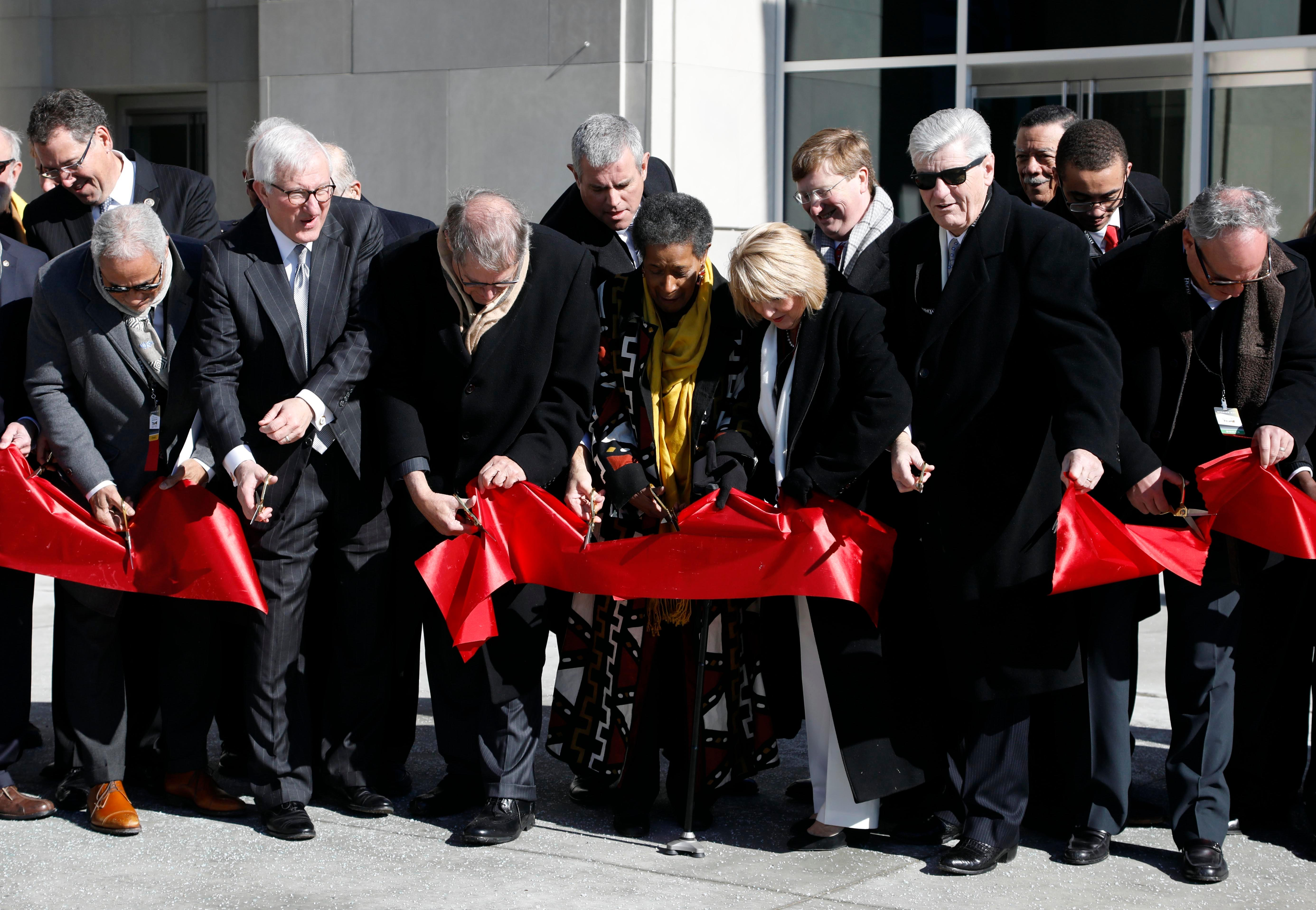Various current and past public officials join Mississippi Gov. Phil Bryant, second from right, and Myrlie Evers, center, civil rights activist and widow of civil rights leader Medgar Evers, as they cut open the oversized ribbon symbolizing the opening of the two museums, the Museum of Mississippi History and the Mississippi Civil Rights Museum, Saturday, Dec. 9, 2017, in Jackson, Miss. (AP Photo/Rogelio V. Solis)