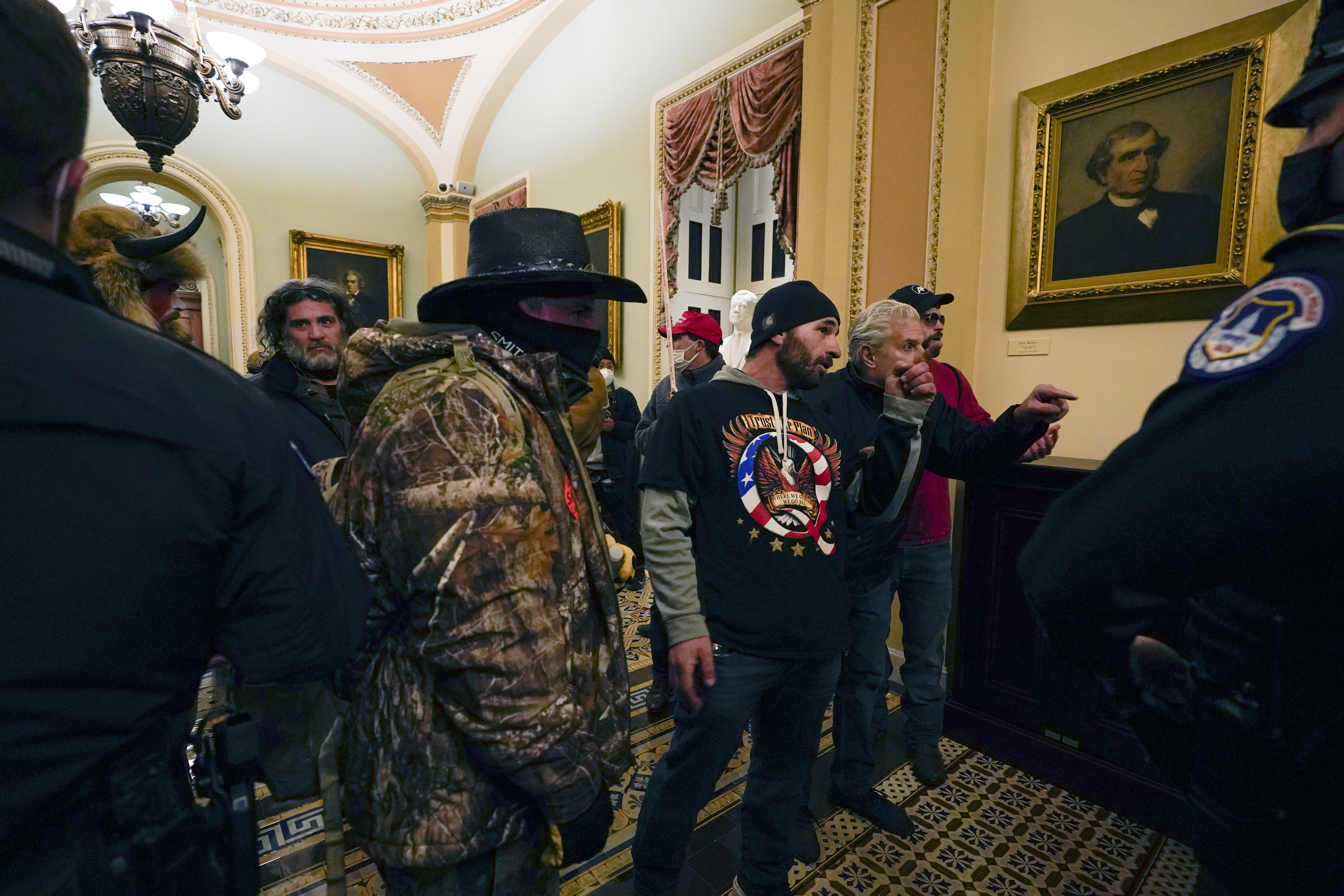 Protesters walk as U.S. Capitol Police officers watch in a hallway near the Senate chamber at the Capitol in Washington, Wednesday, Jan. 6, 2021, near the Ohio Clock. (AP Photo/Manuel Balce Ceneta)