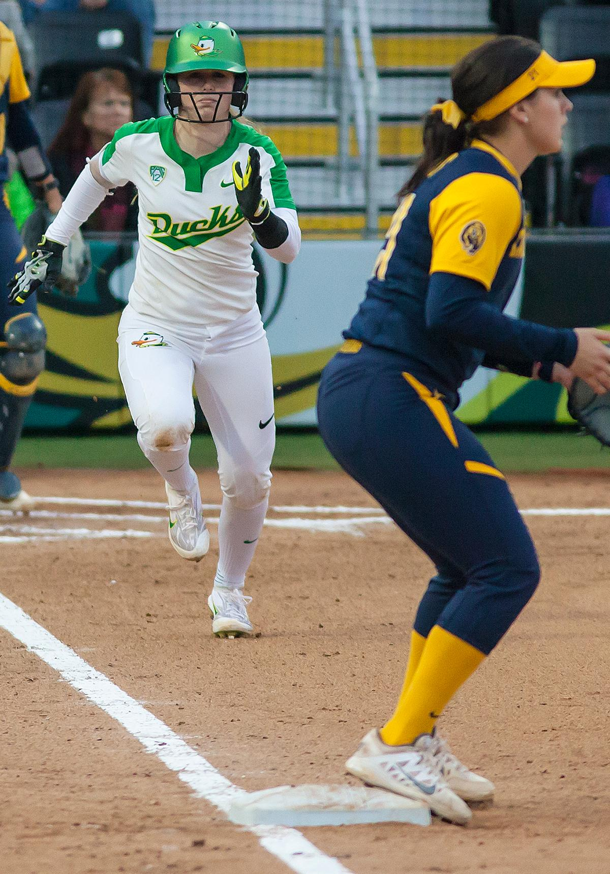 Oregon infielder Jenna Lilley (#00) sprints down the first base line as the ball is passed towards first base. California infielder Bradie Fillmore (#4) catches the ball before tagging out Oregon utility player Lauren Lindvall (#8). In the first of a three game series the Oregon Ducks defeated the California Golden Bears five to one. Photo by Ben Lonergan, Oregon News Lab