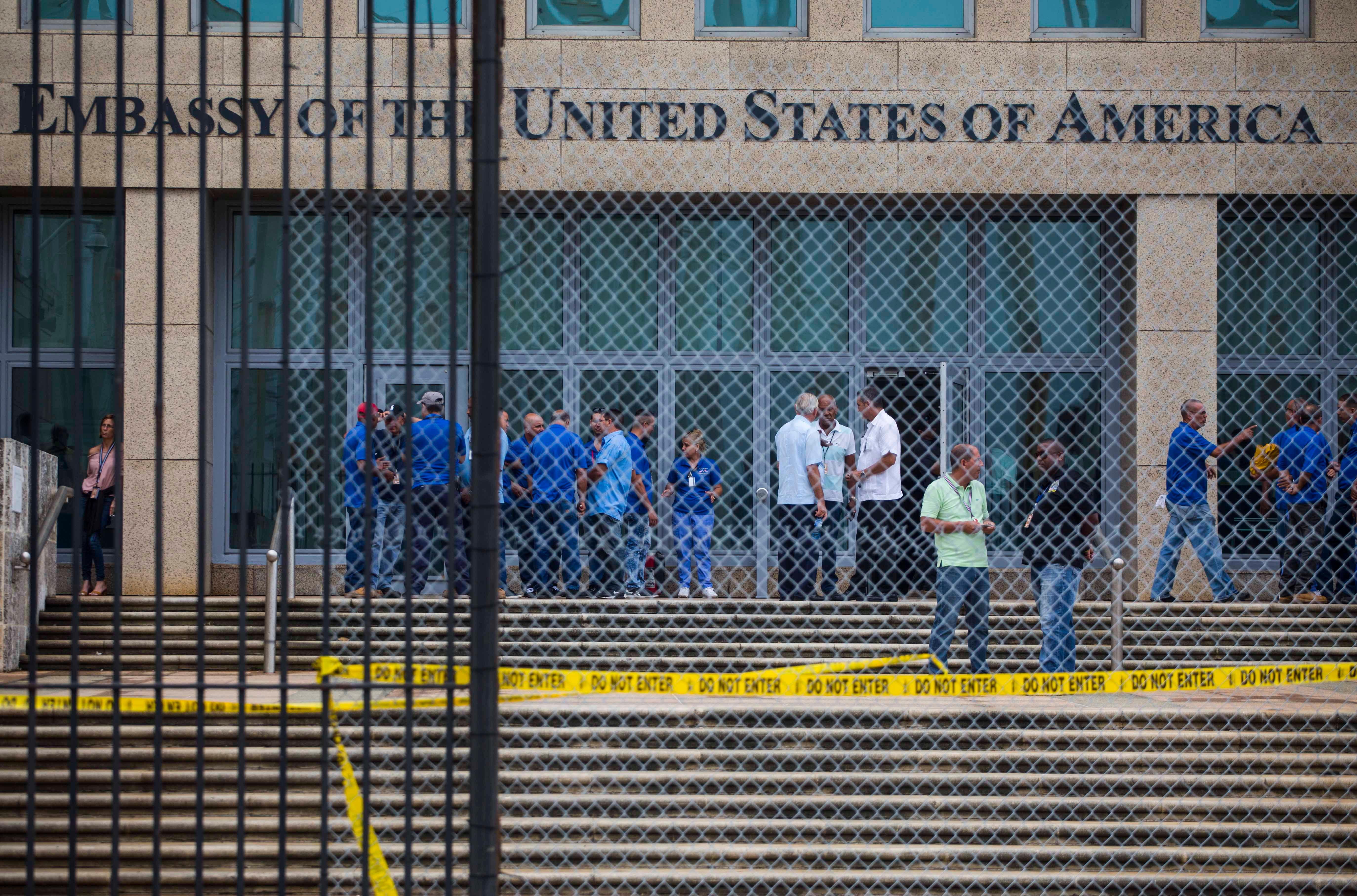 Staff stand within the United States embassy facility in Havana, Cuba, Friday, Sept. 29, 2017. The United States issued an ominous warning to Americans on Friday to stay away from Cuba and ordered home more than half the U.S. diplomatic corps. (AP Photo/Desmond Boylan)