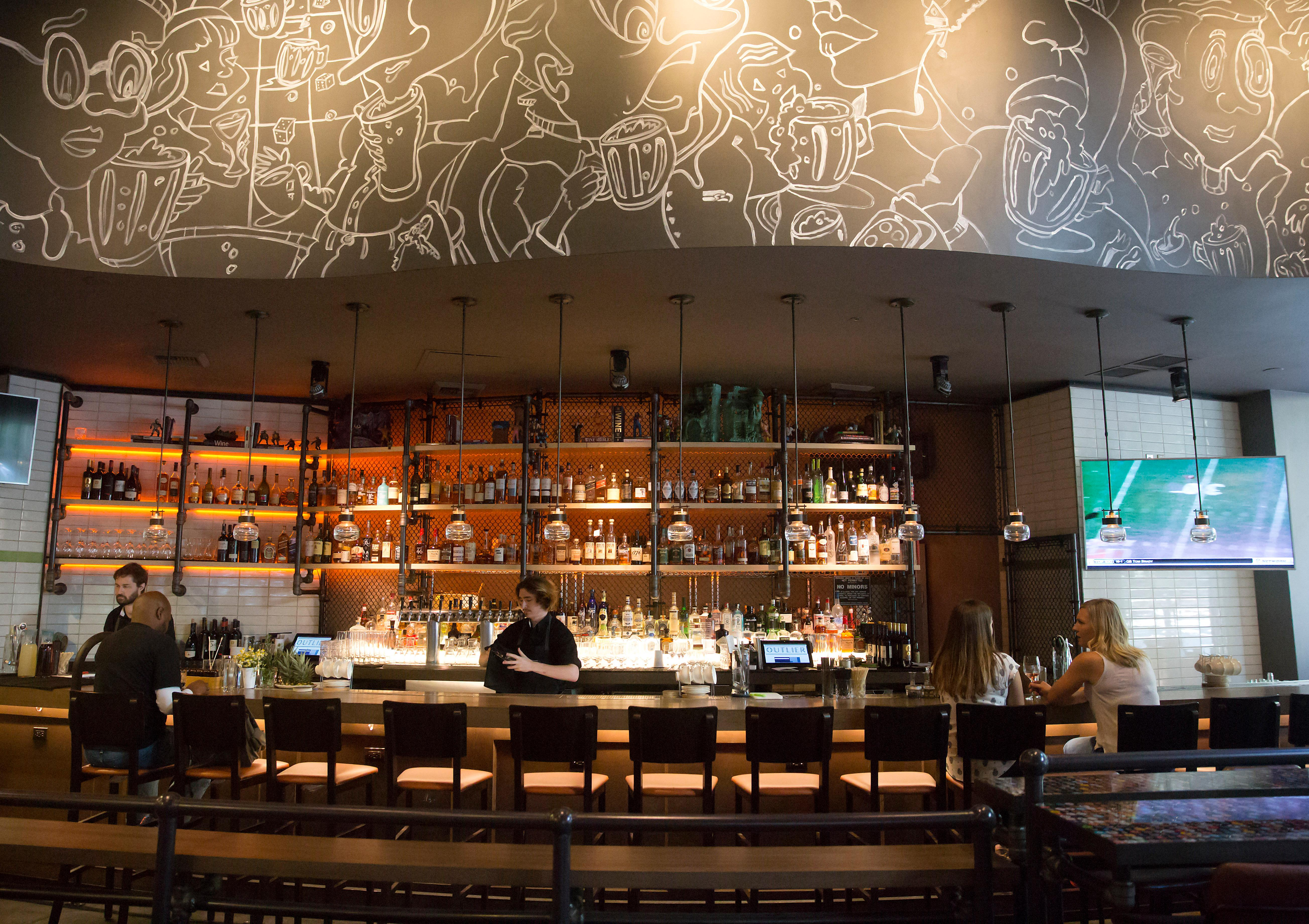 Outlier is located at 1101 4th Ave right by the Hotel Monaco, and pays homage to the fern bars of the 70s and 80s. Street art installations and a wall-sized beer-can . mural define the dining room, and the bustling atmosphere extends onto the seasonal outdoor patio. (Sy Bean / Seattle Refined)