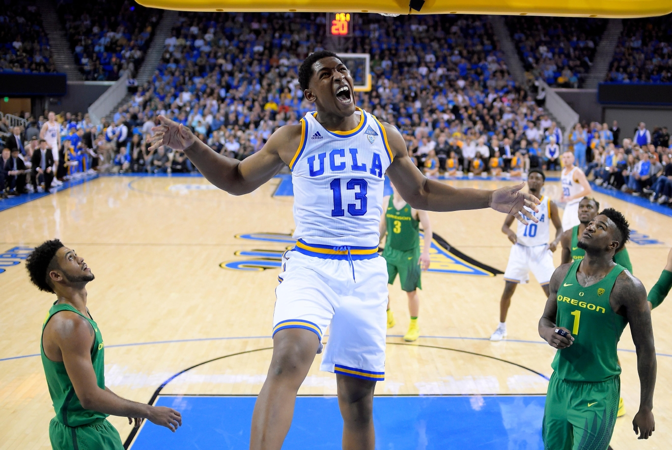 UCLA forward Ike Anigbogu, center, yells as he misses a dunk as Oregon guard Tyler Dorsey, left, and forward Jordan Bell defend during the first half of an NCAA college basketball game, Thursday, Feb. 9, 2017, in Los Angeles. (AP Photo/Mark J. Terrill)