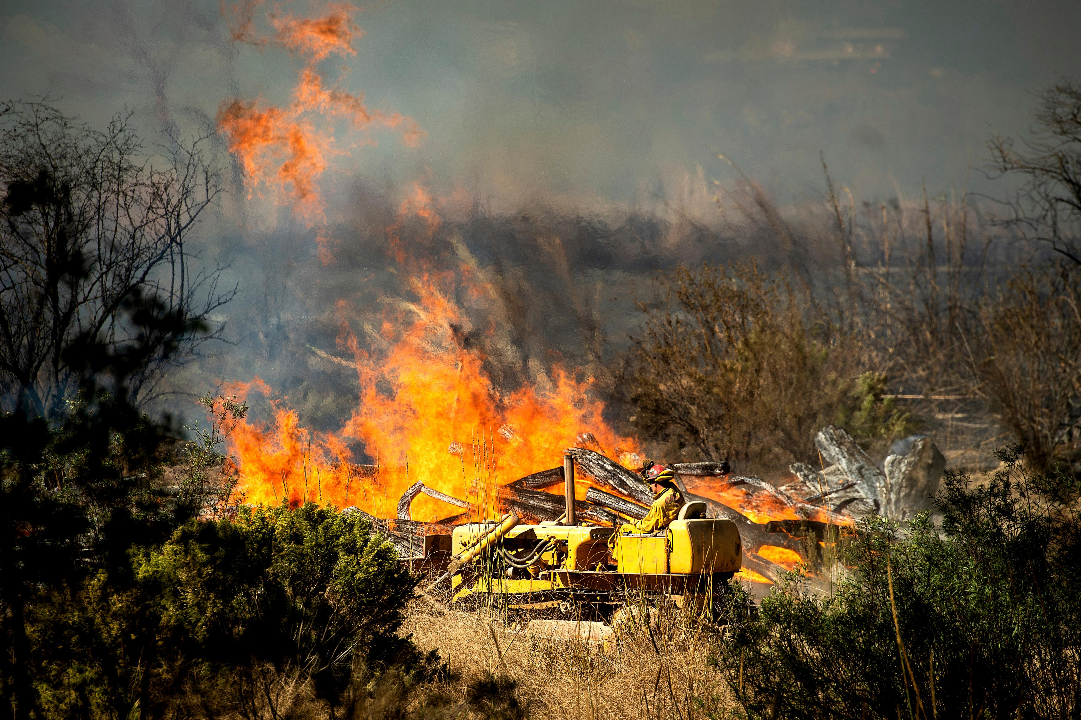 A firefighter creates a fire break as the Maria Fire approaches in Santa Paula, Calif., on Friday, Nov. 1, 2019. According to Ventura County Fire Department, the blaze has scorched more than 8,000 acres and destroyed at least two structures. (AP Photo/Noah Berger)