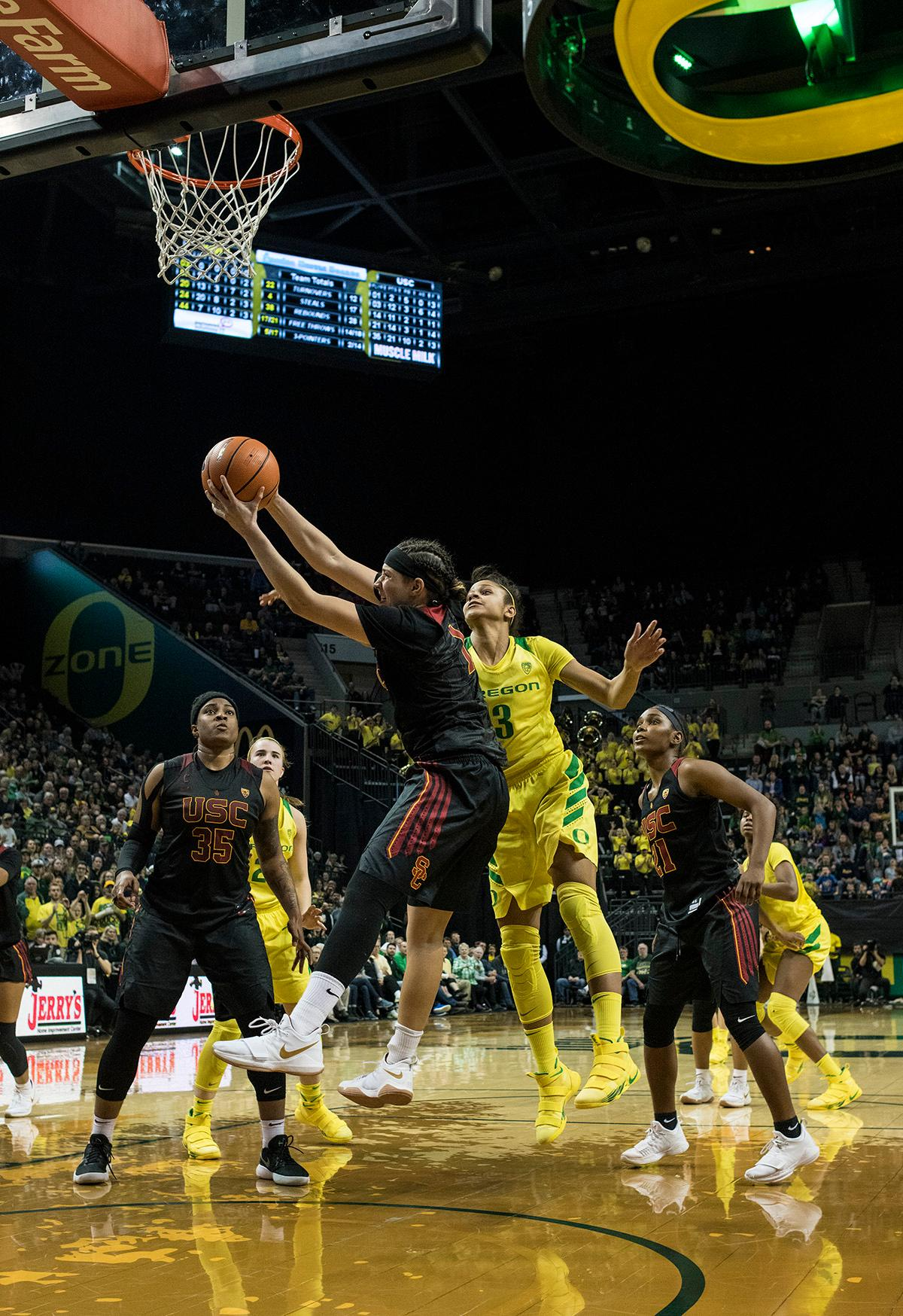 Oregon Ducks Justine Hall (#3) attempts to block a shot. The Oregon Ducks defeated the USC Trojans 80-74 on Friday at Matthew Knight Arena in a game that went into double overtime. Lexi Bando sealed the Ducks' victory by scoring a three-pointer in the closing of the game. Ruthy Hebard set a new NCAA record of 30 consecutive field goals in three straight games, the old record being 28. Ruthy Hebard got a double-double with 27 points and 10 rebounds, Mallory McGwire also had 10 rebounds. The Ducks had four players in double digits. The Ducks are now 24-4, 13-2 in the Pac-12, and are tied for first with Stanford. Photo By Rhianna Gelhart, Oregon News Lab