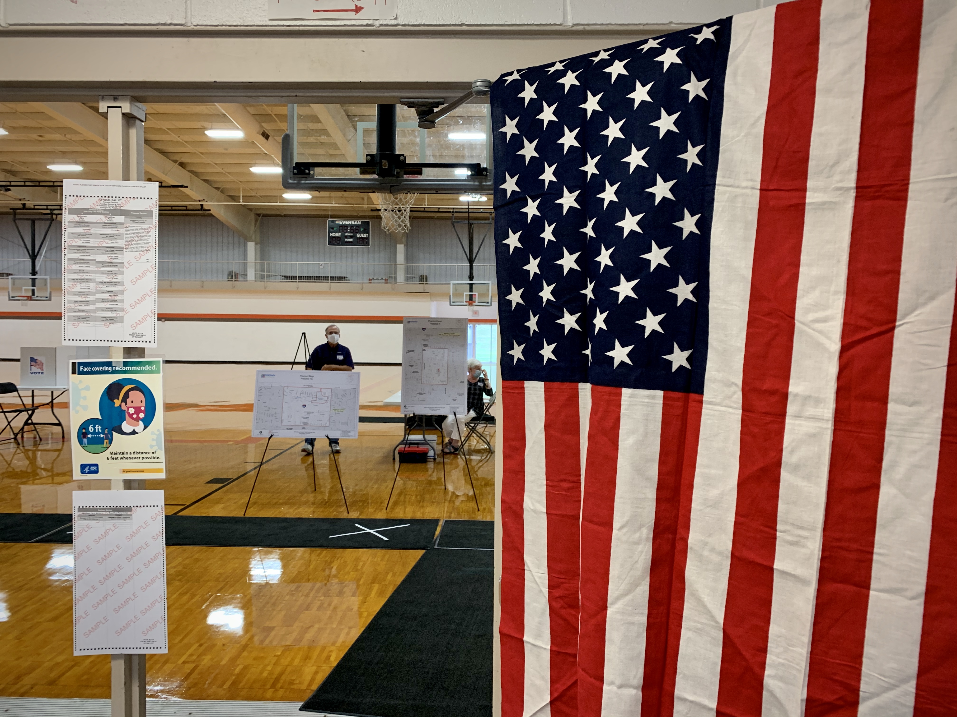 Voters cast their ballots at Portage Northern High School on Tuesday, Aug. 4, 2020. Polling places, with reminders to maintain social distancing because of the COVID-19 pandemic, opened across Michigan at 7 a.m. Tuesday for the state's primary election. (WWMT/Hannah Knowles)