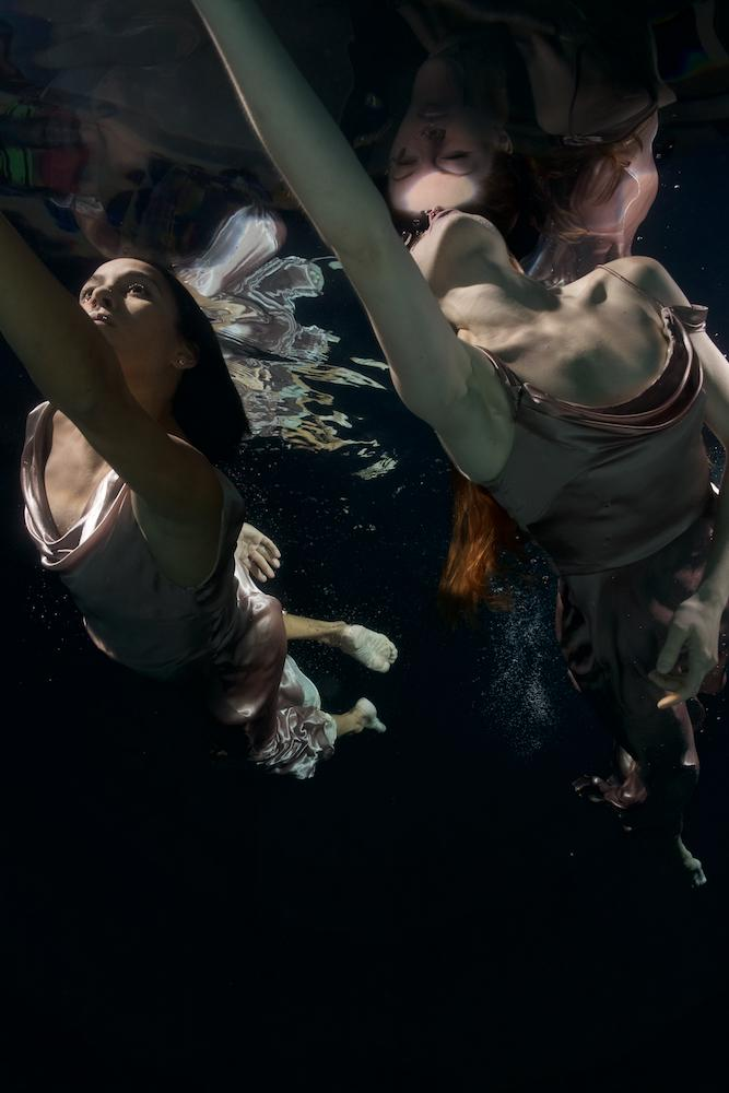 "Statement from artist Tina Gutierrez: ""In this underwater series, a watery environment invites the dancers to yield to the embrace of liquid instead of the greater forces of gravity that they normally experience. The added difficulty of working in the water creates a world of unexpected challenges for the dancer and the photographer. These images are only viewable from below the water and are so fleeting that they can only be captured by the speed of the camera. Due to its calmness yet danger, the water for me has always been a place of peace and solace yet also extreme awareness. The need to make these images is beyond explanation, perhaps as I believe the end result appeals to a deep primal elemental need. Most of the dancers are from the Cincinnati Ballet."" / Cincinnati Ballet dancers Maizyalet Velazquez and Abbey Gonzalez Kay / Image: Tina Gutierrez // Published: 3.28.20<p></p>"