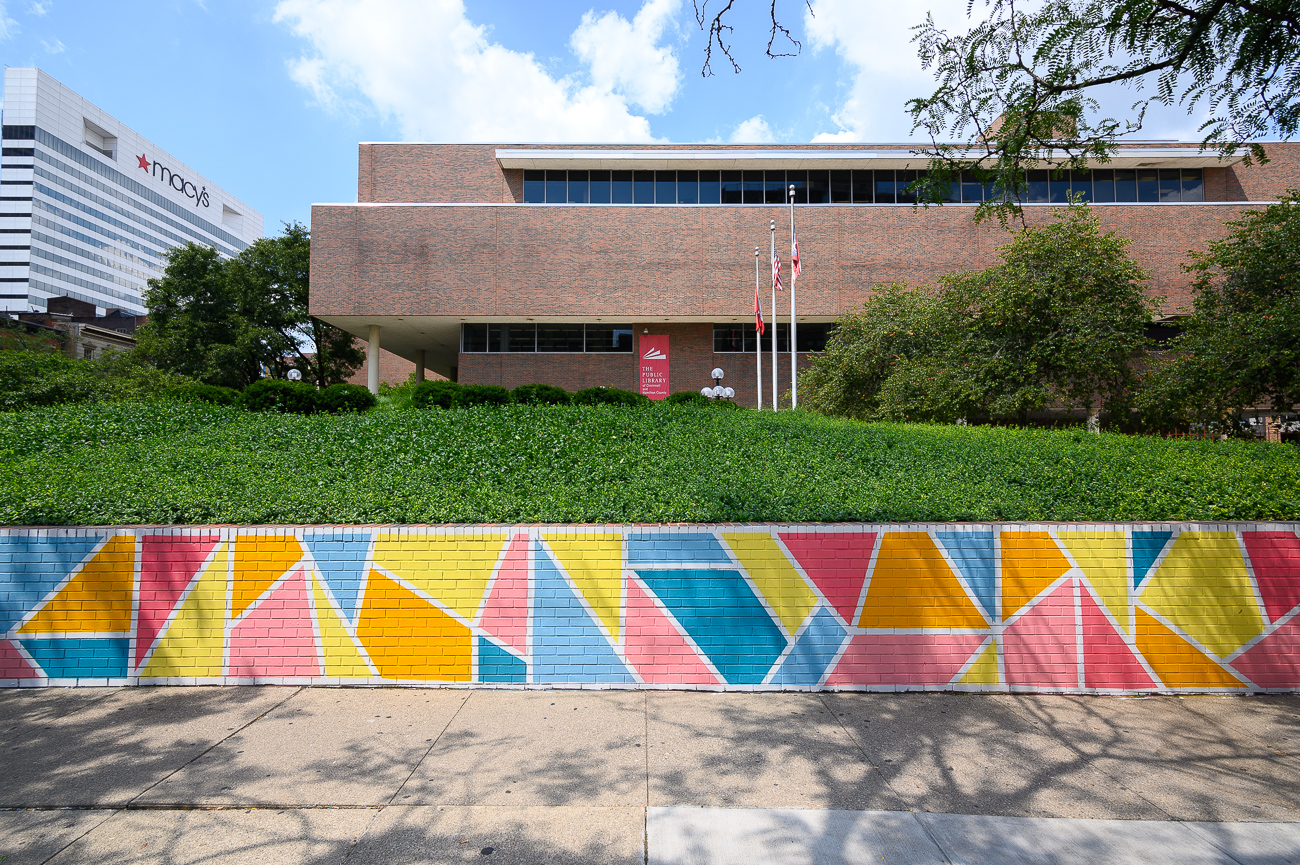 "The Main Library let Josh do a geometric landscape on a low wall facing Walnut Street. The mural features three distinct colors: shades of gold to represent the queen in ""Queen City,"" shades of blue to represent the Ohio River, and shades of pink to represent flying pigs. / Image: Phil Armstrong, Cincinnati Refined // Published: 8.10.19"