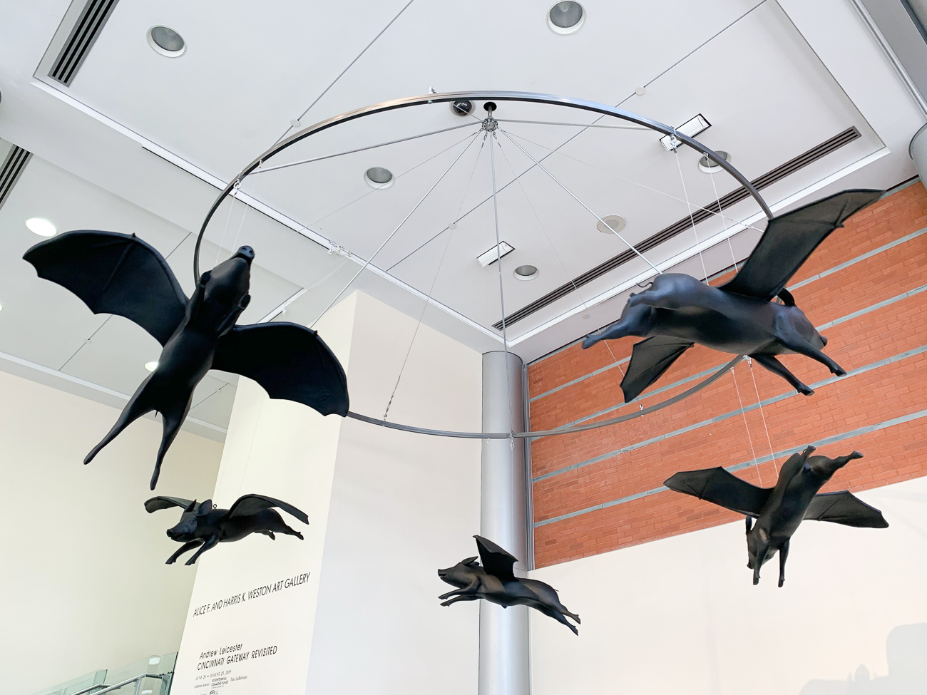 A sculpture on the street level gallery features twirling flying pigs with bat wings. Designed by Andrew Leicester years later, the piece represents an incapacitated political machine that's unable to progress, circling back on itself over and over again. It's a response to the short-lived controversy that circled the flying pig back in the late 80s. / Image: Phil Armstrong // Published: 8.13.19