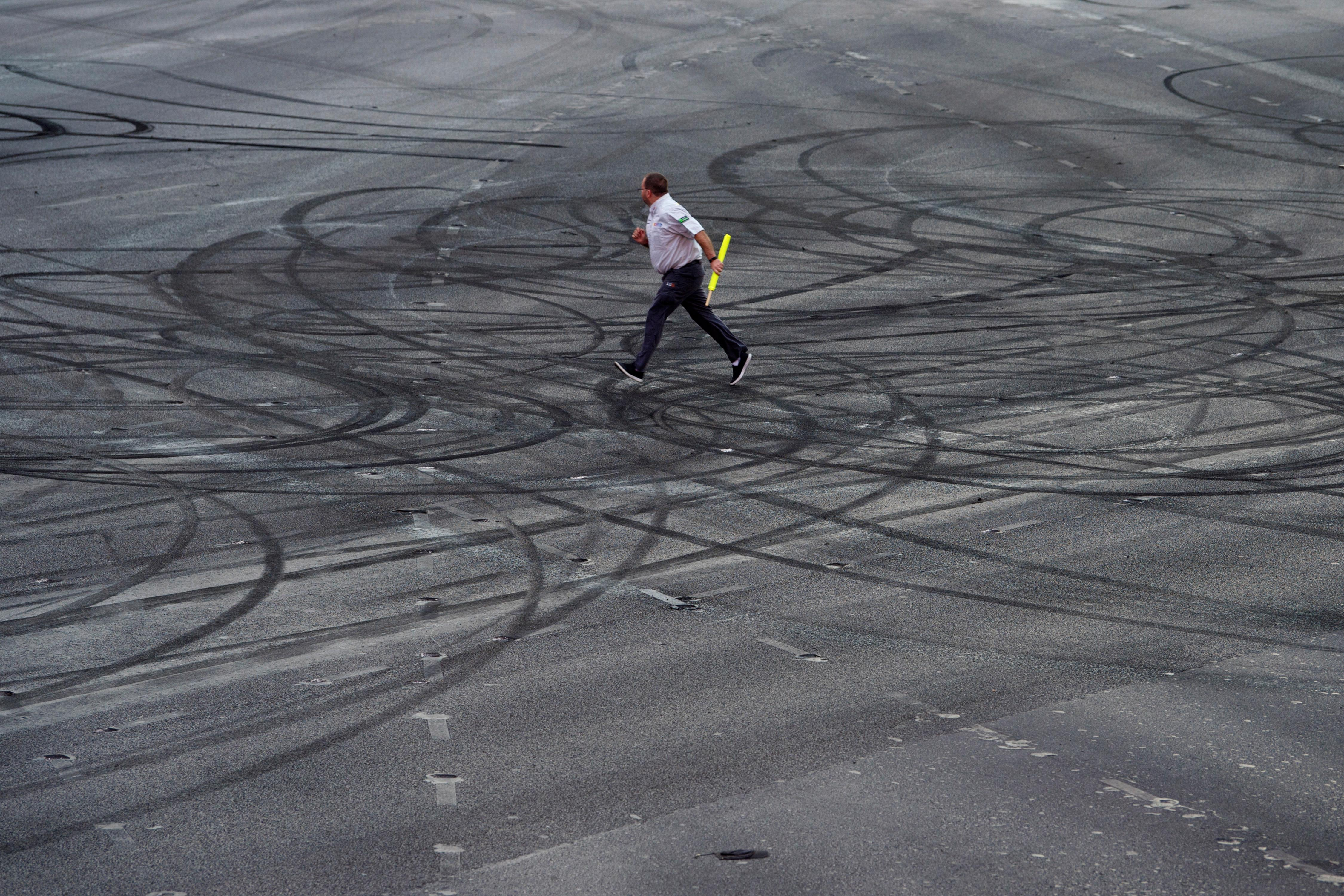 A NASCAR official runs across skid marks during the NASCAR Victory Lap on the Las Vegas Strip being held as part of Champions Week Wednesday, November 29, 2017. CREDIT: Sam Morris/Las Vegas News Bureau