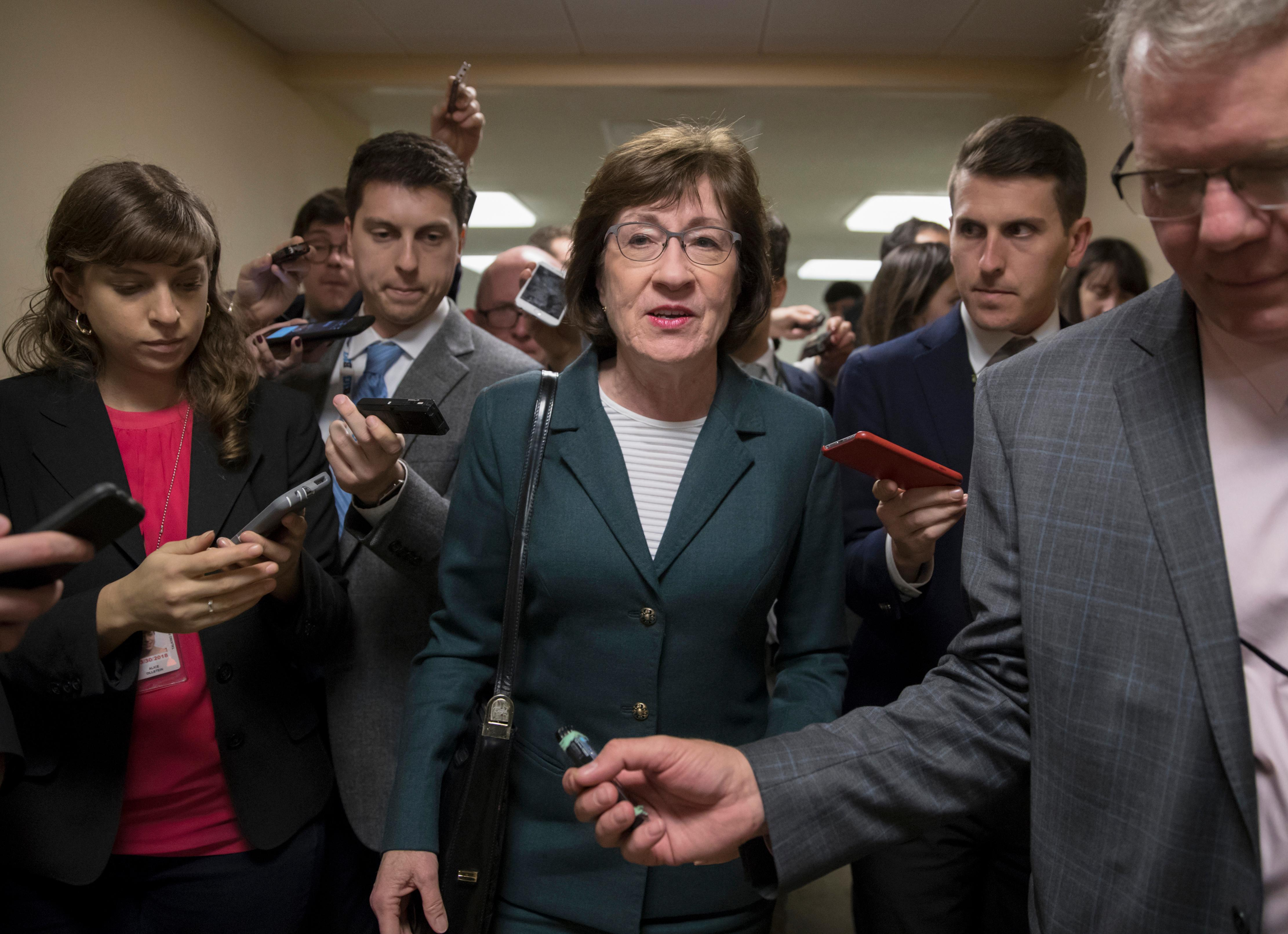 With reporters looking for updates, Sen. Susan Collins, R-Maine, and other senators rush to the chamber to vote on amendments as the Republican leadership works to craft their sweeping tax bill, on Capitol Hill in Washington, Thursday, Nov. 30, 2017. (AP Photo/J. Scott Applewhite)