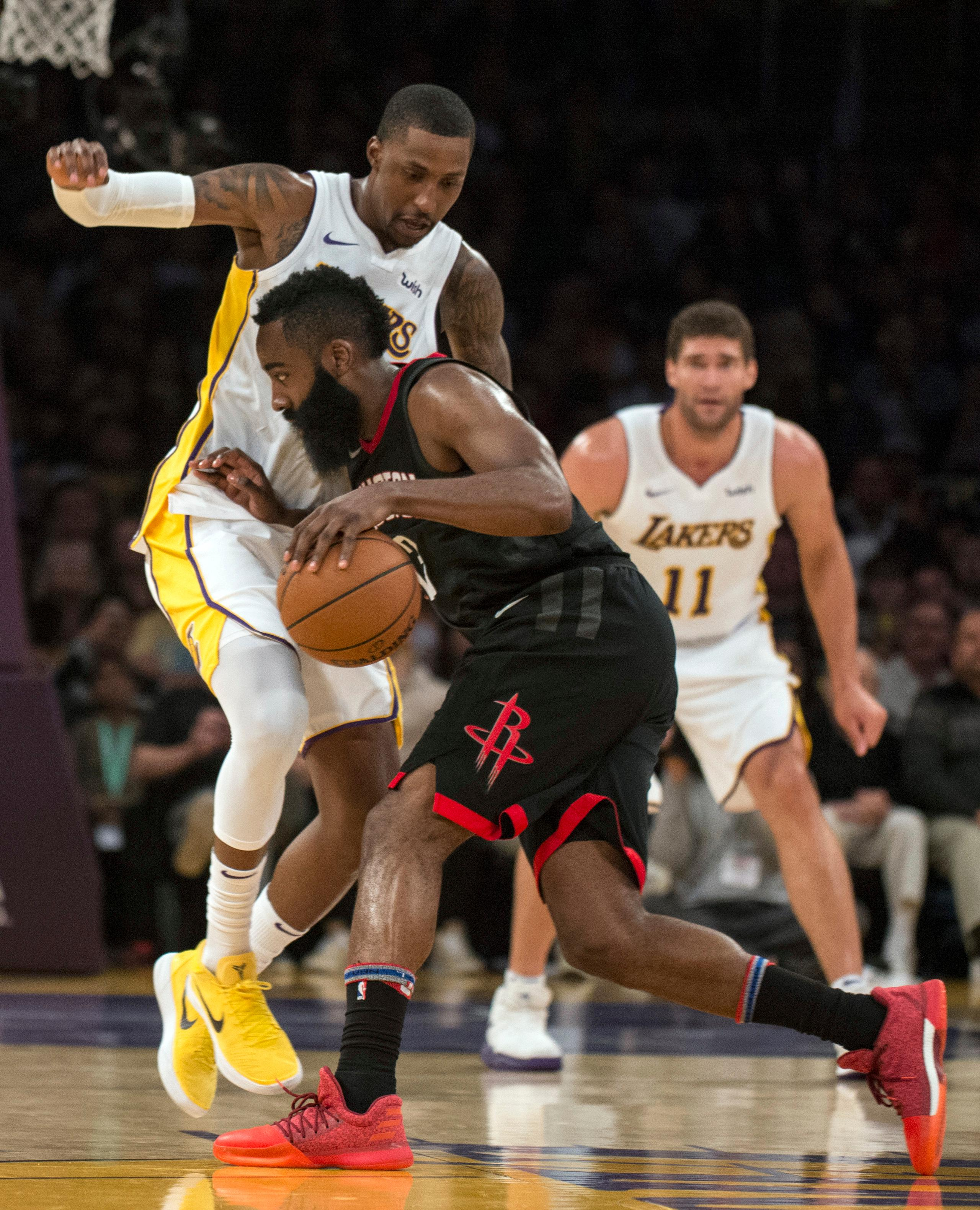 Los Angeles Lakers guard Kentavious Caldwell-Pope, left, defends Houston Rockets guard James Harden, center, during the second half of an NBA basketball game Sunday, Dec. 3, 2017, in Los Angeles. (AP Photo/Kyusung Gong)