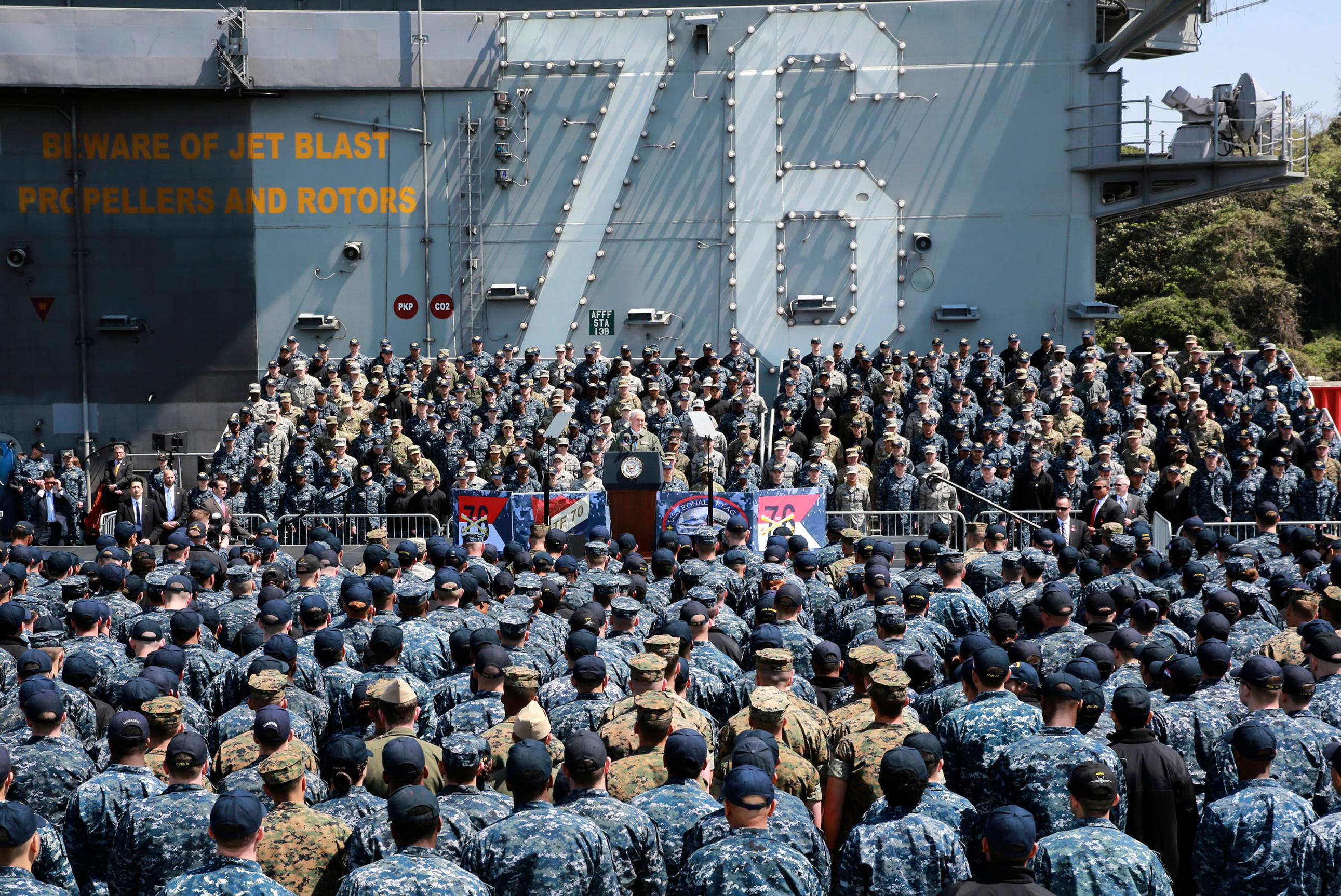 U.S. Vice President Mike Pence, center, speaks to U.S. servicemen and Japanese Self-Defense Forces personnel on the flight deck of U.S. navy nuclear-powered aircraft carrier USS Ronald Reagan, at the U.S. Navy's Yokosuka base in Yokosuka, south of Tokyo, Wednesday, April 19, 2017. Japan is drawing up emergency responses in case of a North Korea missile strike. A number of municipalities are testing community alarm systems and planning evacuation drills as concerns run high around U.S. military bases. Both Japan and South Korea are home to tens of thousands of U.S. troops. (AP Photo/Eugene Hoshiko)