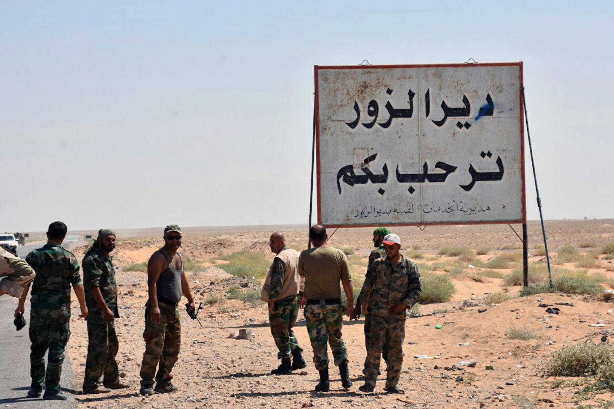 "File - in this file photo released online on Sept. 3, 2017, by the Syrian official news agency SANA, shows Syrian troops and pro-government gunmen standing next to a placard in Arabic which reads, ""Deir el-Zour welcomes you,"" in the eastern city of Deir el-Zour, Syria.  Syria state media says pro-government troops have seized the Islamic state stronghold town of Mayadeen after weeks of fighting for the oil-rich eastern Deir el-Zour province that straddles the border with Iraq. (SANA via AP, File)"
