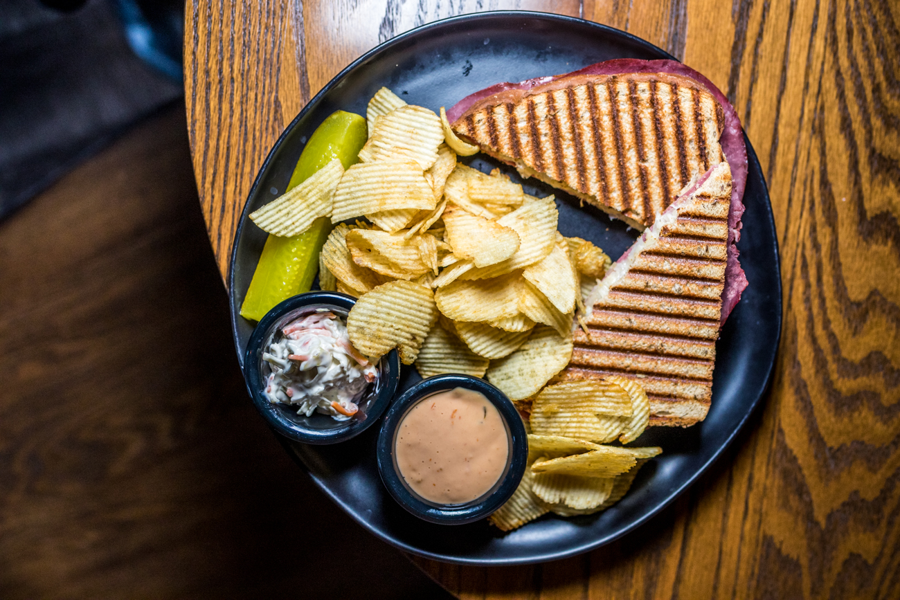 Reuben Melt: lean corn beef, Wisconsin swiss, sauerkraut, thousand island dressing, rye bread served with chips, slaw, and a pickle / Image: Catherine Viox // Published: 2.25.21