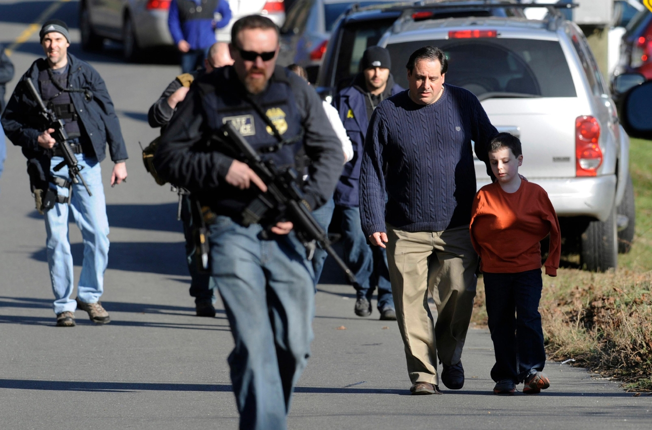 FILE - In this Friday, Dec. 14, 2012 file photo, parents leave a staging area after being reunited with their children following a shooting at the Sandy Hook Elementary School in Newtown, Conn., where Adam Lanza fatally shot 27 people, including 20 children. (AP Photo/Jessica Hill, File)