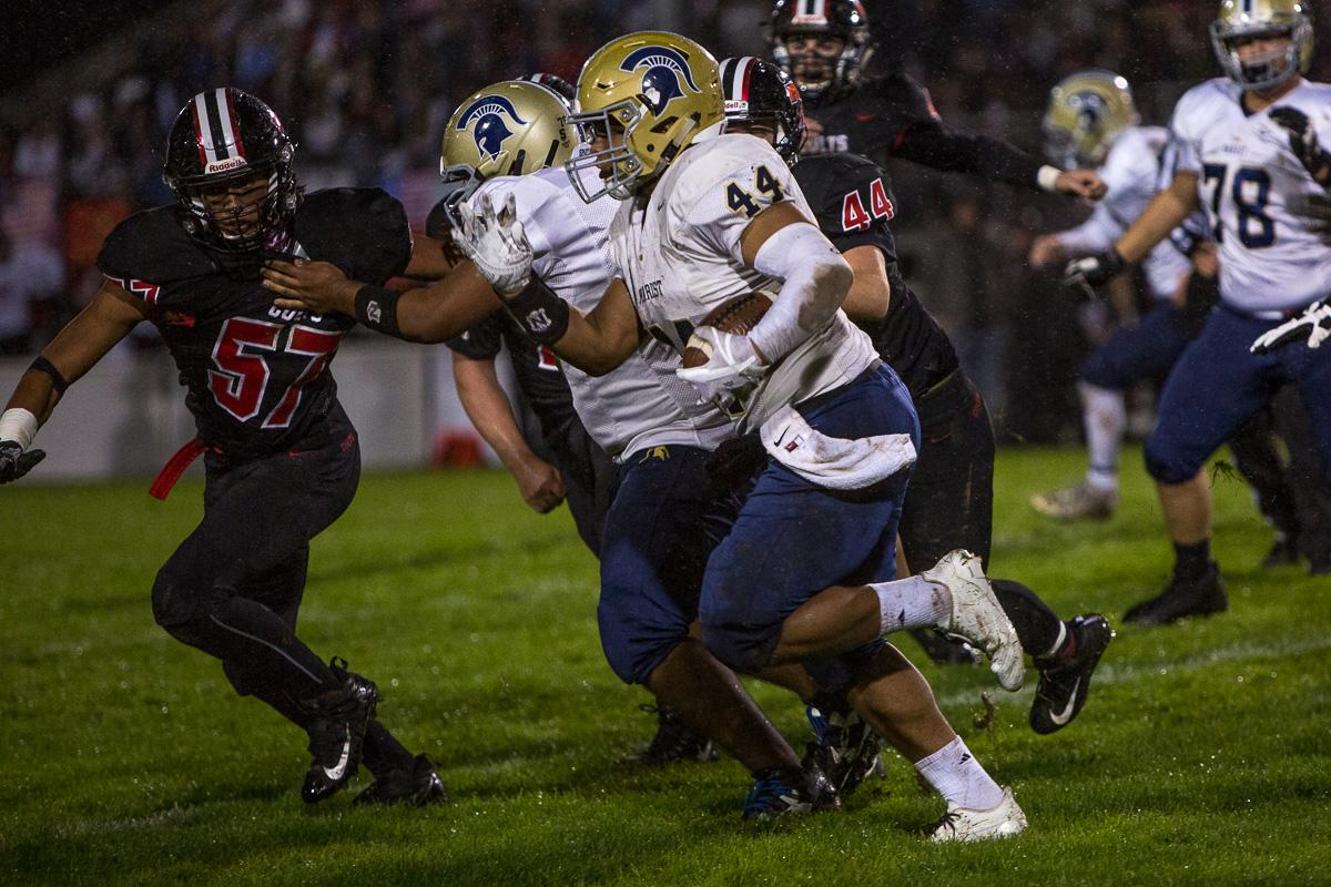 Marist Spartans running back Aavonte Clark (#44) runs the ball as his teammates attempt to block Thurston's defense. The Thurston Colts defeated the Marist Catholic Spartans 50 – 14 to seal second place in their conference at Thurston High School on Friday, October 13. Photo by Kit MacAvoy, Oregon News Lab