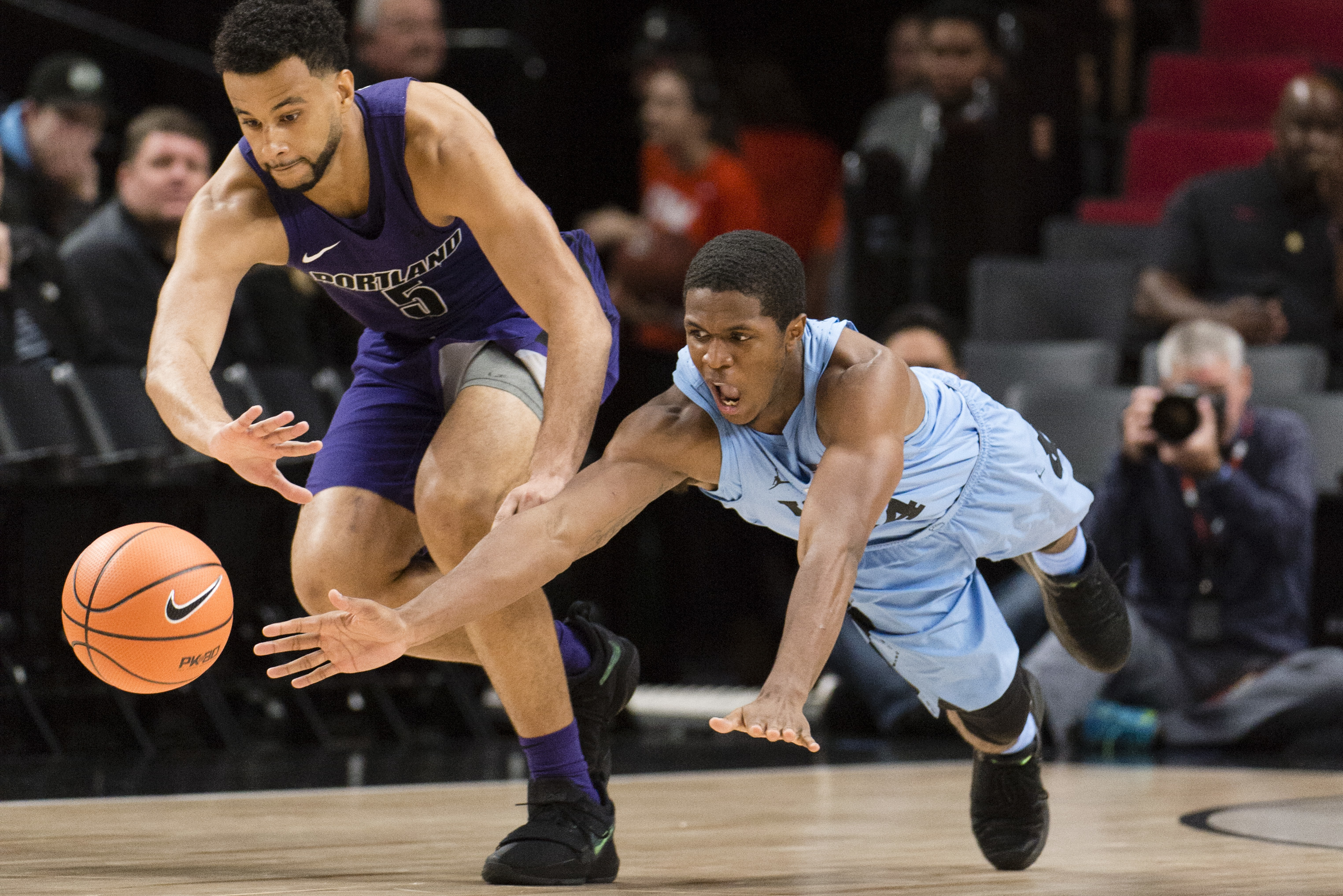 North Carolina guard Kenny Williams, right, dives for a loose ball against Portland guard D'Marques Tyson, left, during the first half in an NCAA college basketball game at the Phil Knight Invitation Tournament, in Portland, Ore., Thursday, Nov. 23, 2017. (AP Photo/Troy Wayrynen)