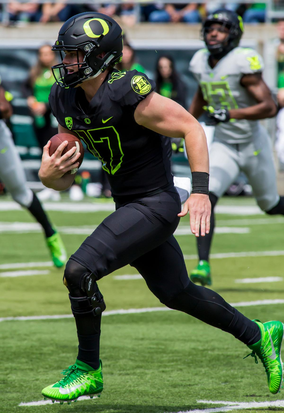 Team Brave quarter back Braxton Burmeister (#17) runs with the ball in a attempt to outpace the defense. The 2017 Oregon Ducks Spring Game provided fans their first glimpse at the team under new Head Coach Willie Taggart's direction. Team Free defeated Team Brave 34-11 on a sunny dat at Autzen Stadium in Eugene, Oregon. Photo by Ben Lonergan, Oregon News Lab