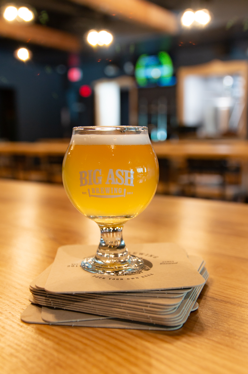 Patrons of Big Ash carry their own tab as soon as they walk in. The cashier links their credit card to a beer card, which then becomes the swiping ticket to food and beverages. From there, you can pour your own beer in the tap room, serving yourself a pint or just a sample to try different beers—you only pay by the ounce at the end of the night. But if you don't feel like getting a drink yourself, there are also beer meisters walking around the taproom who can take your drink order. / Image: Elizabeth A. Lowry // Published: 9.25.19
