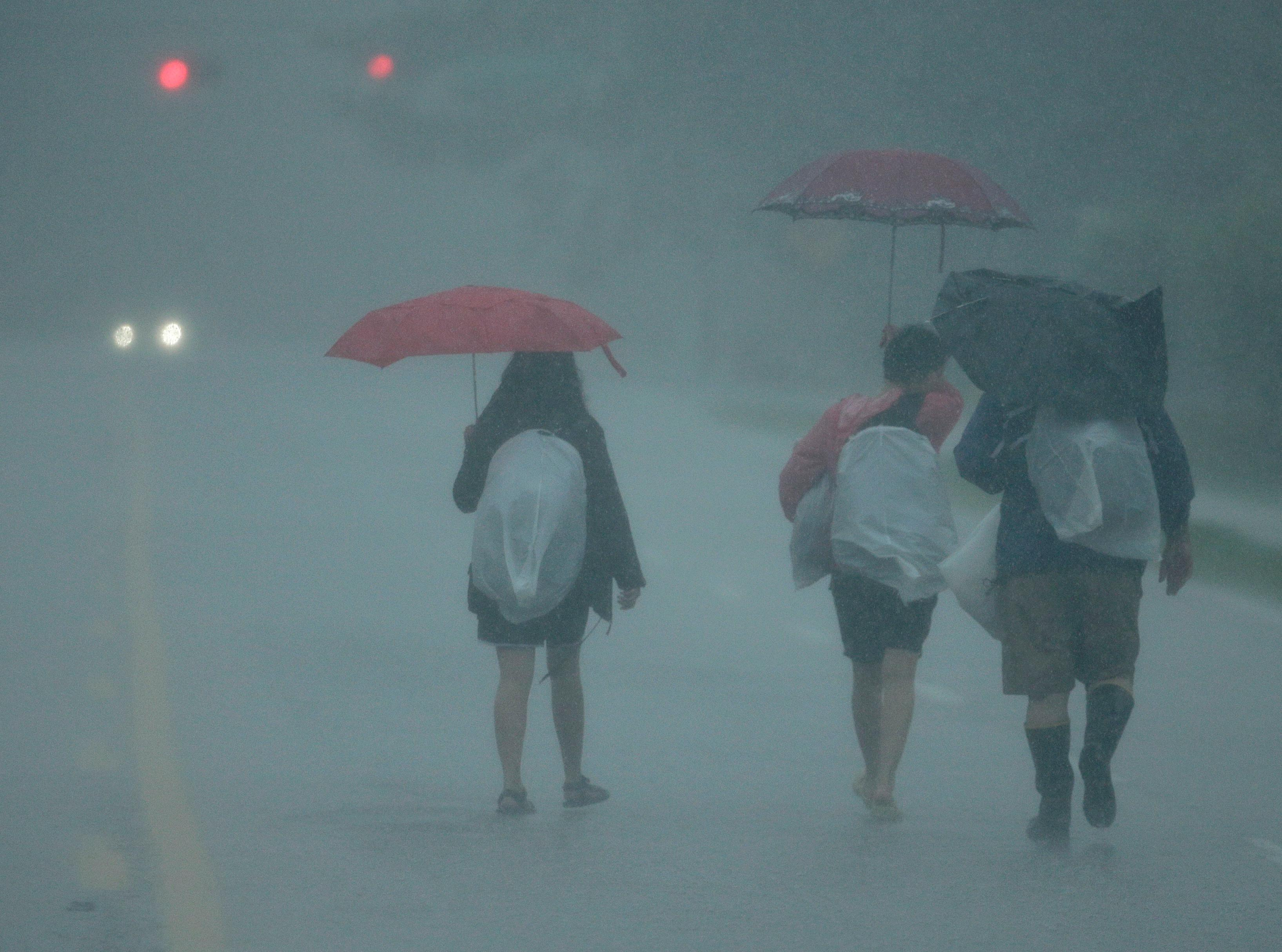 People walk in heavy rain as they evacuate floodwaters from Tropical Storm Harvey on Sunday, Aug. 27, 2017, in Houston, Texas. (AP Photo/Charlie Riedel)