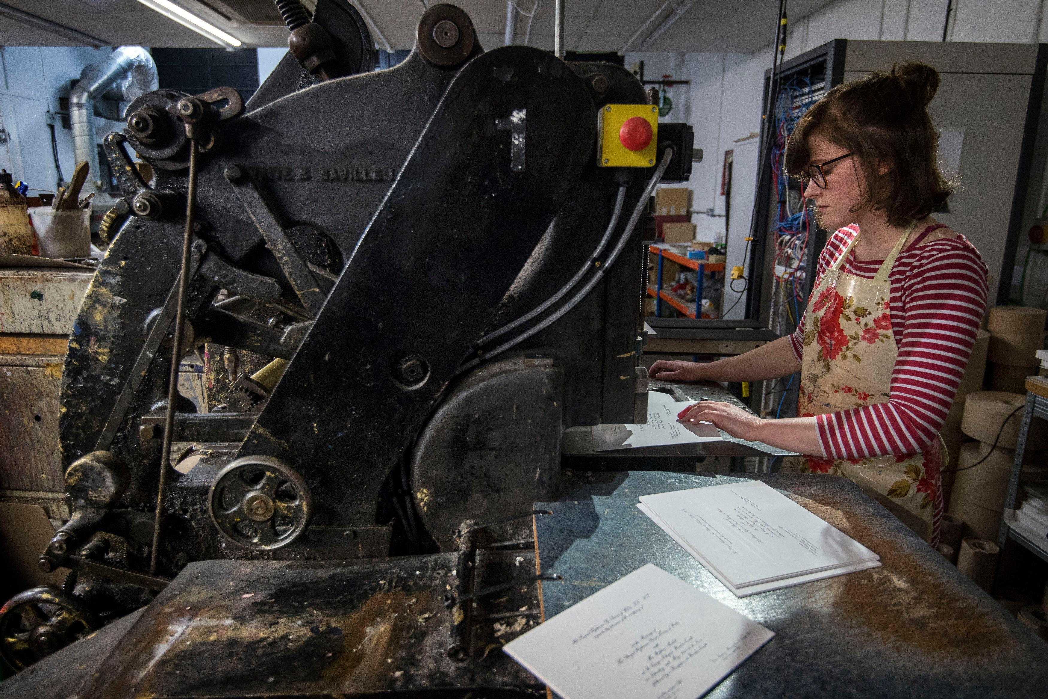 Lottie Small use the die stamping press at the workshop of Barnard and Westwood in London, who are printing the invitations for Prince Harry and Meghan Markle's wedding in May  Thursday March 22, 2018. Prince Harry and Meghan will get married at St George's Chapel  in Windsor Castle on Saturday  May 19. (Victoria Jones/Pool via AP)