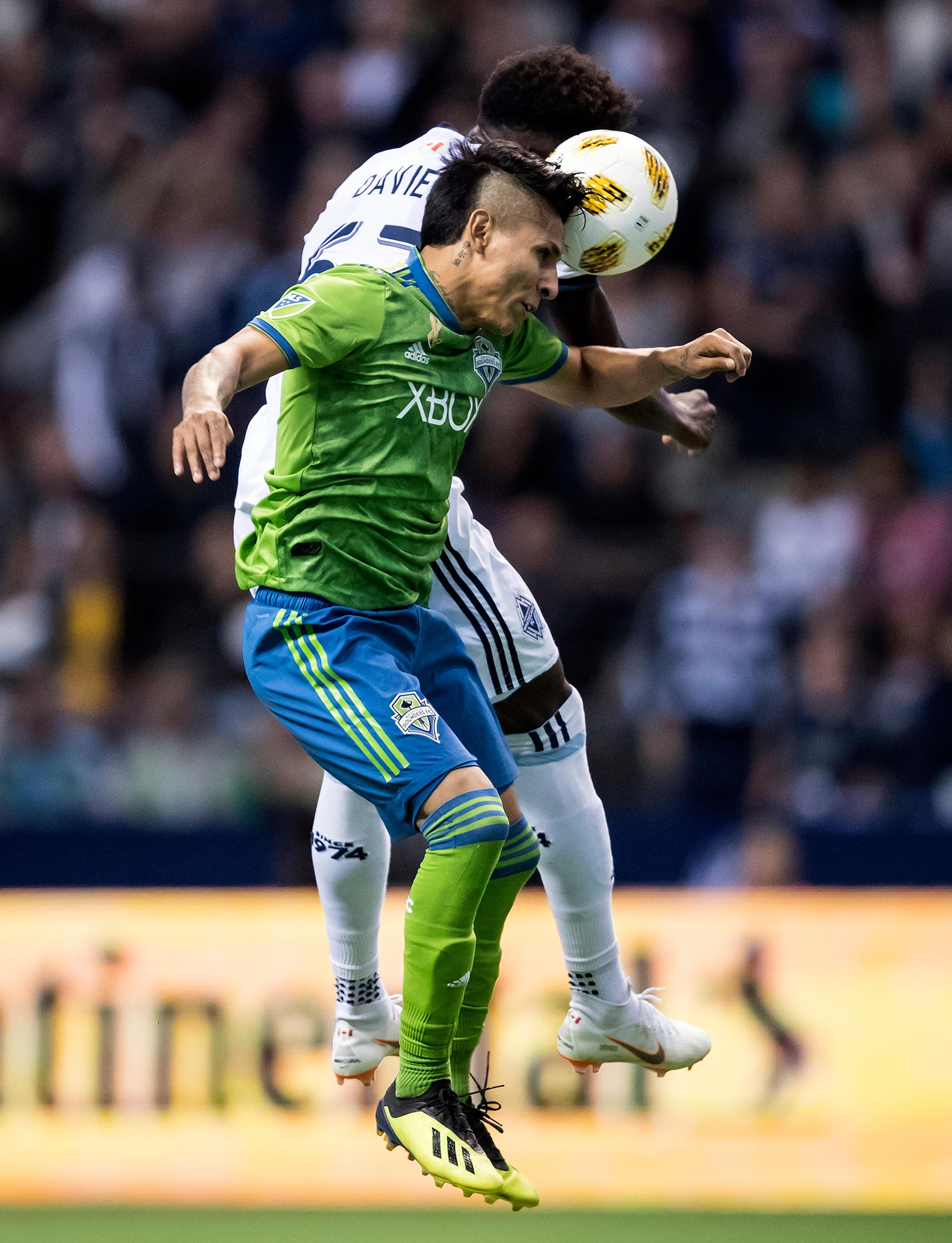 Seattle Sounders' Raul Ruidiaz, front, and Vancouver Whitecaps' Alphonso Davies vie for the ball during the first half of an MLS soccer match, Saturday, Sept. 15, 2018, in Vancouver, British Columbia. (Darryl Dyck/The Canadian Press via AP)
