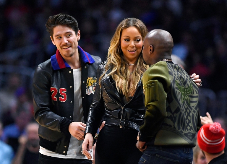 Singer Mariah Carey, center, talks with boxer Floyd Mayweather Jr., right, as Bryan Tanaka standsnear by during the second half of an NBA basketball game between the Atlanta Hawks and the Los Angeles Clippers on Wednesday, Feb. 15, 2017, in Los Angeles. The Clippers won 99-84. (AP Photo/Mark J. Terrill)