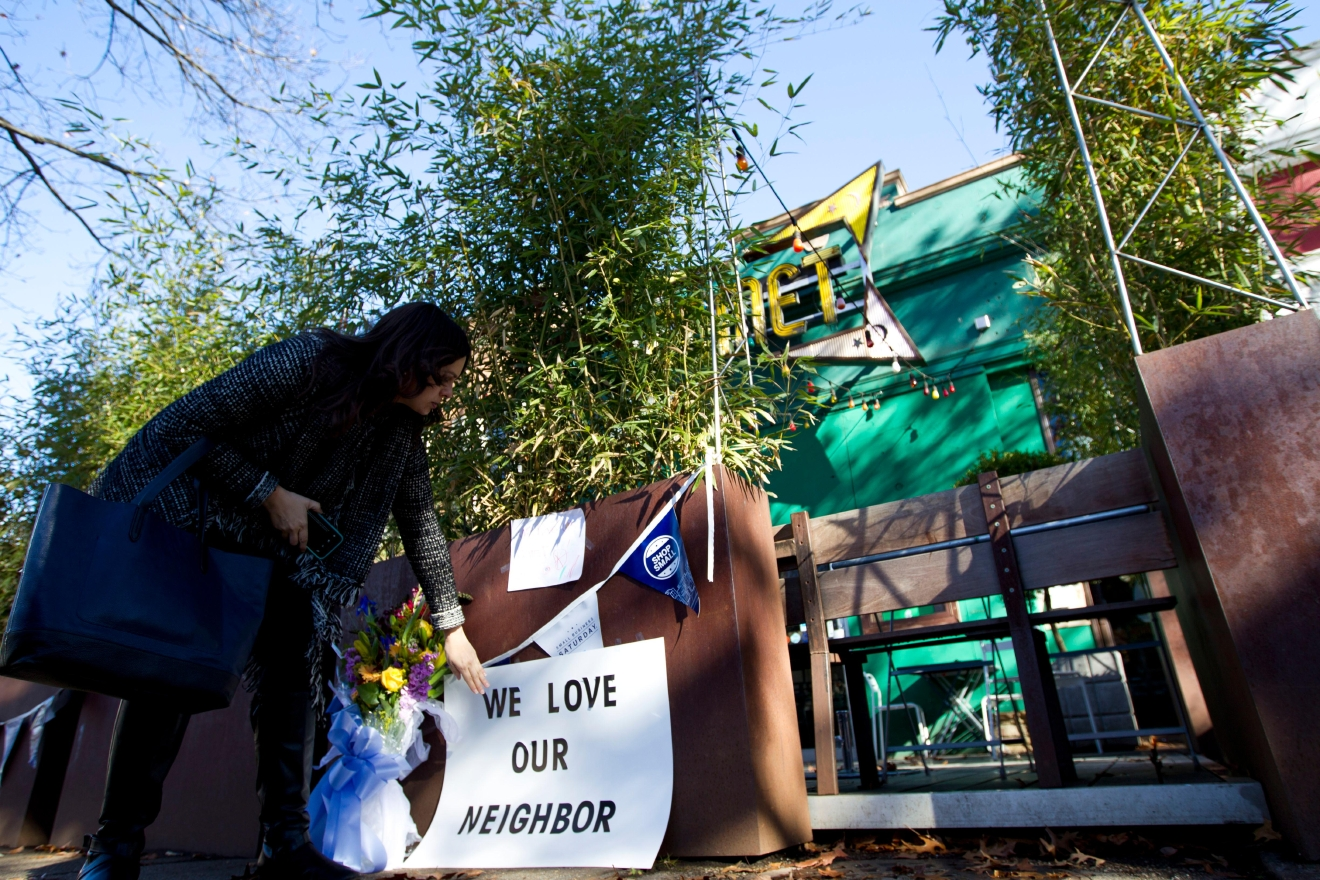 Meighan Stone places a support banner with flowers outside the door of Comet Ping Pong pizza shop, in Washington, Monday, Dec. 5, 2016.  ( AP Photo/Jose Luis Magana)