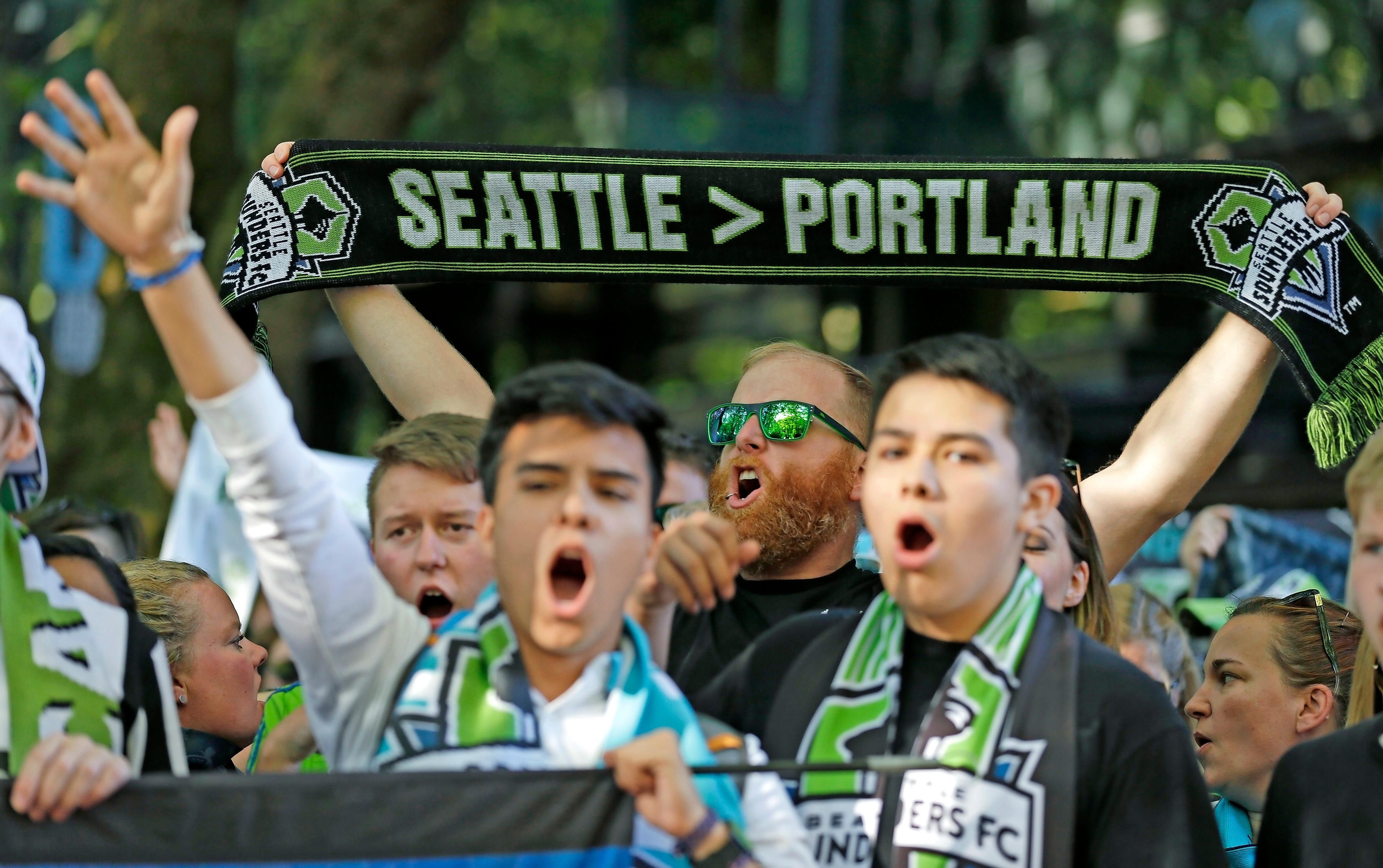 FILE - In this Aug. 27, 2017, file photo, a Seattle Sounders supporter holds up a scarf as he takes part in the traditional March to the Match before an MLS soccer match against the Portland Timbers in Seattle. The Timbers host the Sounders on Sunday in the 100th meeting between the two rivals from the Pacific Northwest. (AP Photo/Ted S. Warren, File)