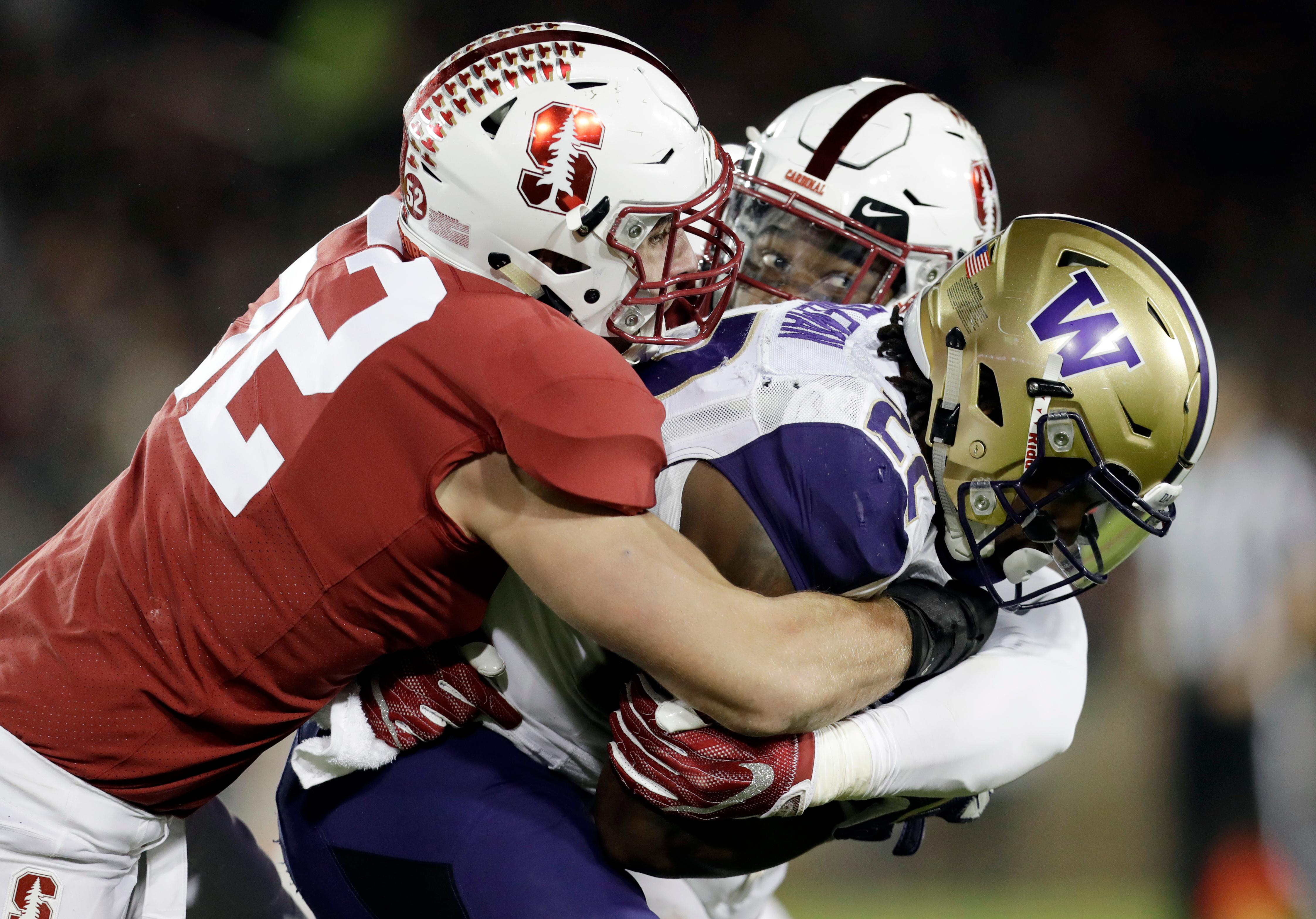 Washington running back Lavon Coleman, right, is tackled by Stanford cornerback Alameen Murphy, center, and linebacker Casey Toohill (52) during the first half of an NCAA college football game Friday, Nov. 10, 2017, in Stanford, Calif. (AP Photo/Marcio Jose Sanchez)