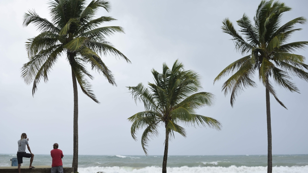 People stand near the shore before the arrival of Hurricane Irma, in luquillo, Puerto Rico, Wednesday, Sept. 6, 2017. Irma roared into the Caribbean with record force early Wednesday, its 185-mph winds shaking homes and flooding buildings on a chain of small islands along a path toward Puerto Rico, Cuba and Hispaniola and a possible direct hit on densely populated South Florida. (AP Photo/Carlos Giusti)