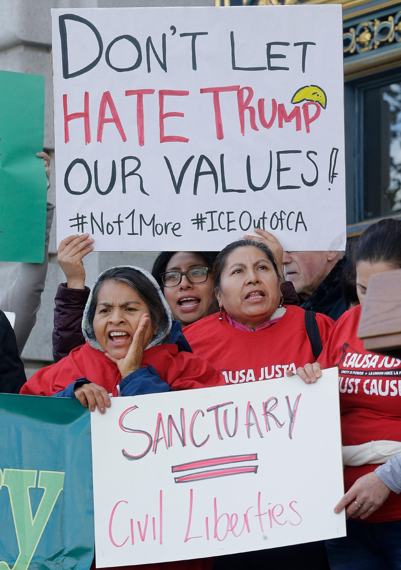 "Protesters hold signs as they yell at a rally outside of City Hall in San Francisco, Wednesday, Jan. 25, 2017. President Donald Trump moved aggressively to tighten the nation's immigration controls Wednesday, signing executive actions to jumpstart construction of his promised U.S.-Mexico border wall and cut federal grants for immigrant-protecting ""sanctuary cities."" (AP Photo/Jeff Chiu)"
