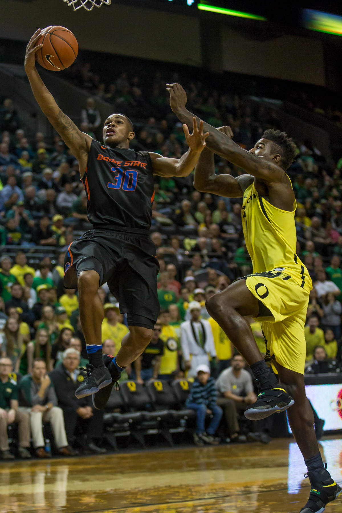 Boise State guard Paris Austin (#30) jumps past Oregon forward Jordan Bell (#1) on his way to the rim. After trailing for most of the game, the Oregon Ducks defeated the Boise State Broncos 68-63. Photo by Dillon Vibes