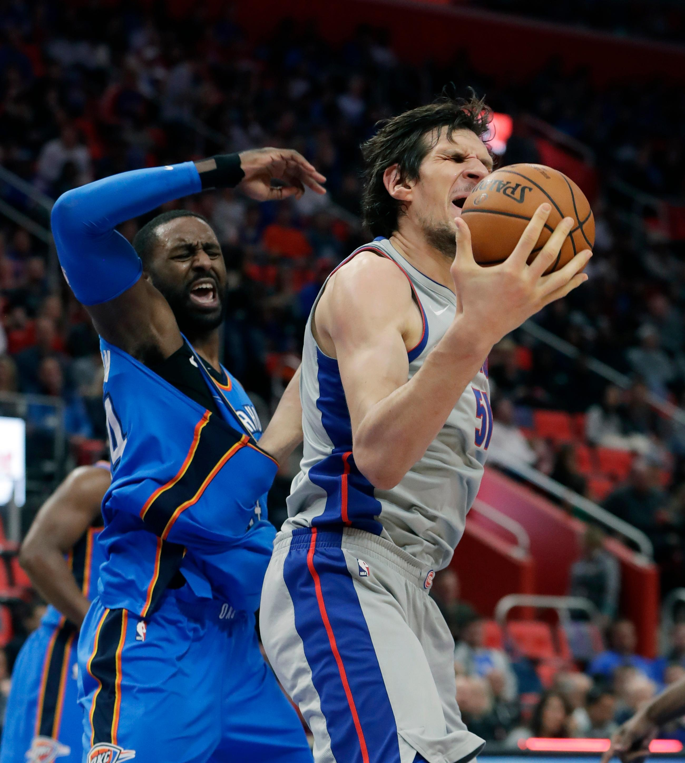 Detroit Pistons center Boban Marjanovic, right, and Oklahoma City Thunder forward Patrick Patterson react as Marjanovic recovers a rebound but has his left arm stuck in Patterson's jersey during the first half of an NBA basketball game Saturday, Jan. 27, 2018, in Detroit. (AP Photo/Carlos Osorio)