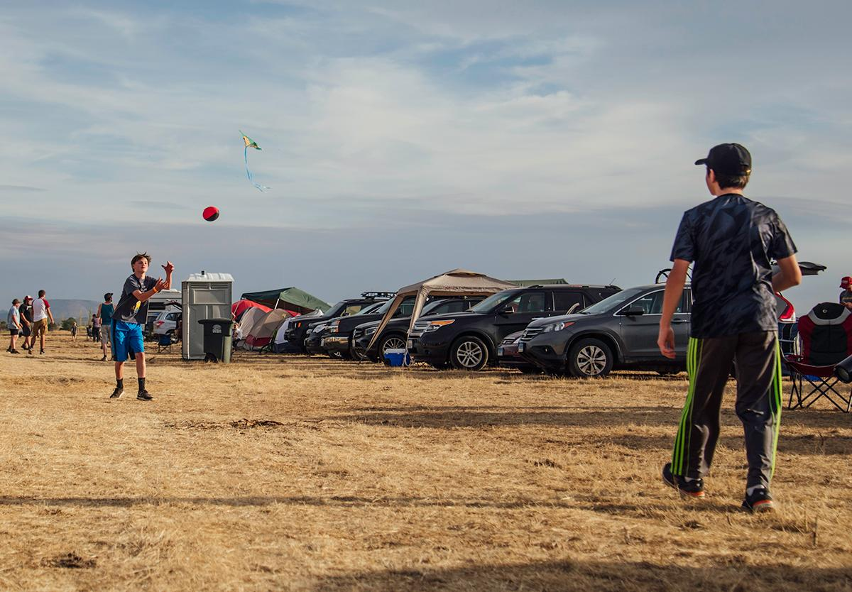 Connor and Nathaniel play football in front of their campsite as a way to stay entertained and active before the eclipse. Photo by Cheyenne Thorpe, Oregon News Lab