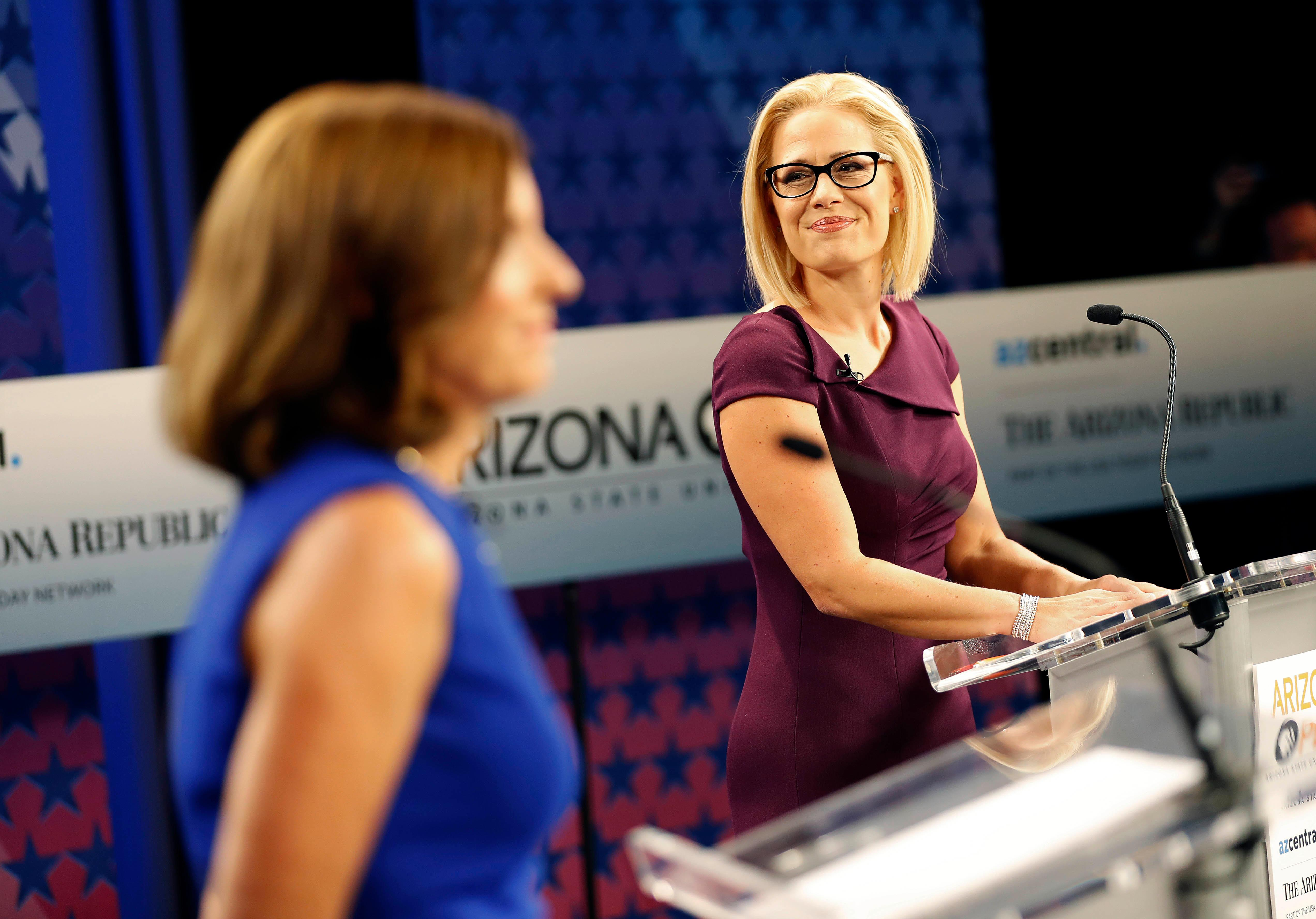 "Republican Rep. Martha McSally(left) accused her Democratic opponent, Rep. Kyrsten Sinema, of supporting ""treason,"" citing a 15-year-old radio interview. McSally attacked Sinema for protesting the wars in Iraq and Afghanistan and referenced a 2003 radio interview in which the host engaged in a lengthy, rambling hypothetical that ends with him asking Sinema if she'd be OK with him joining the Taliban.""I don't care if you want to do that, go ahead,"" Sinema replied in that interview, reported by CNN last week. (AP Photo/Matt York)"