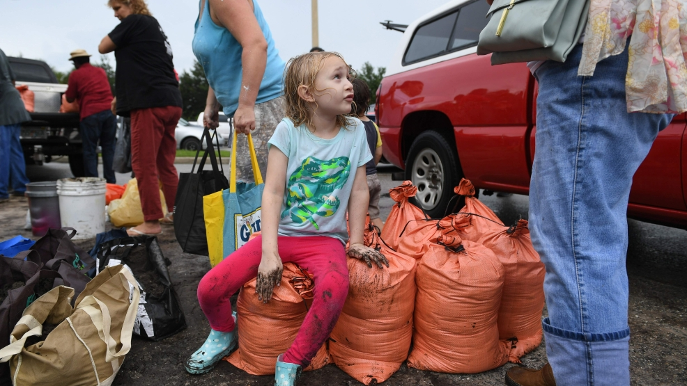 Sophia Johnson, 6, talks to her mom, Kace Johnson, of Sarasota, Florida, after they finished filling ten sandbags with dirt provided by Sarasota County at the Newtown Estates Rec Center to prepare for Hurricane Irma. The Johnsons got the last ten sandbags Wednesday shortly after noon, before the county ran out of sandbags. The county had plenty of dirt, but people had to start bringing their own bags or containers. The county was expecting another delivery of sandbags on Thursday. [Herald-Tribune staff photo / Mike Lang]