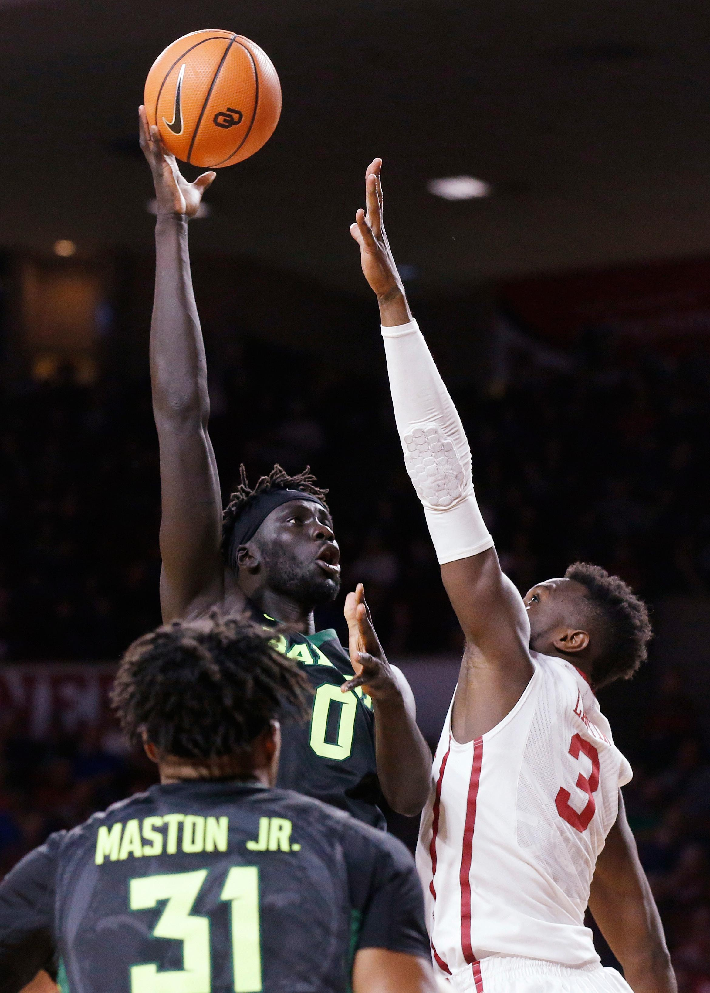 Baylor forward Jo Lual-Acuil Jr. (0) shoots over Oklahoma forward Khadeem Lattin, right, during the first half of an NCAA college basketball game in Norman, Okla., Tuesday, Jan. 30, 2018. (AP Photo/Sue Ogrocki)