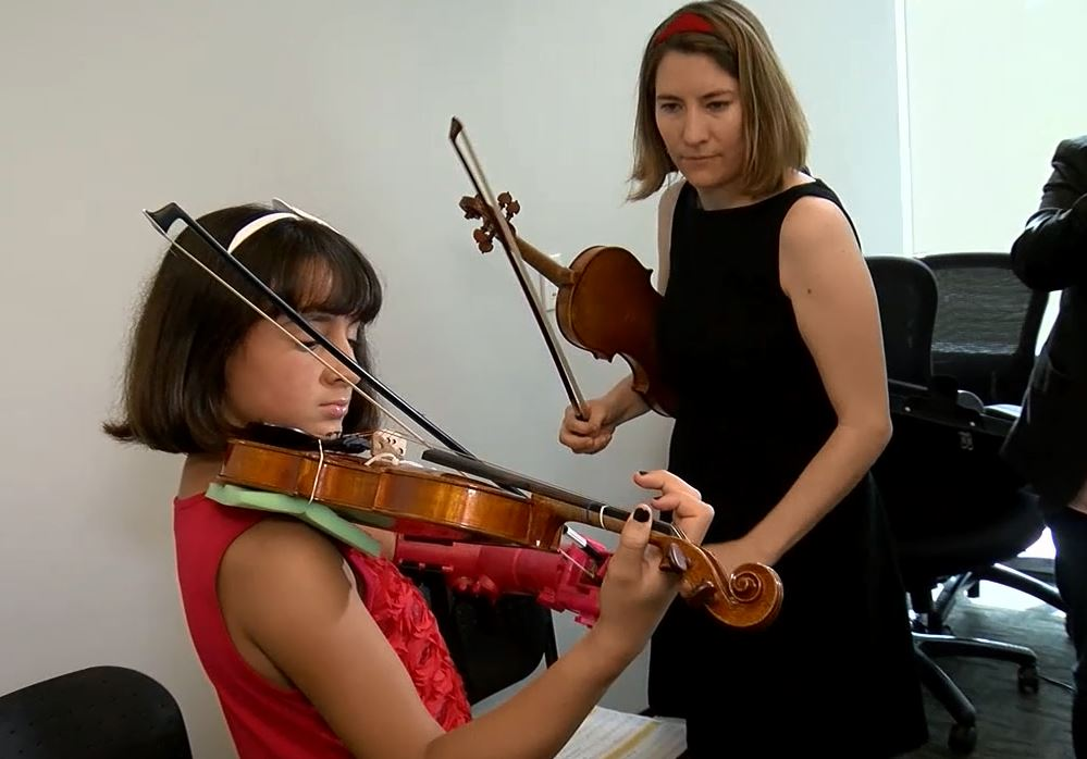 Isabella Cabrera learns to play the violin with her new, 3D-printed hand. (ABC7)