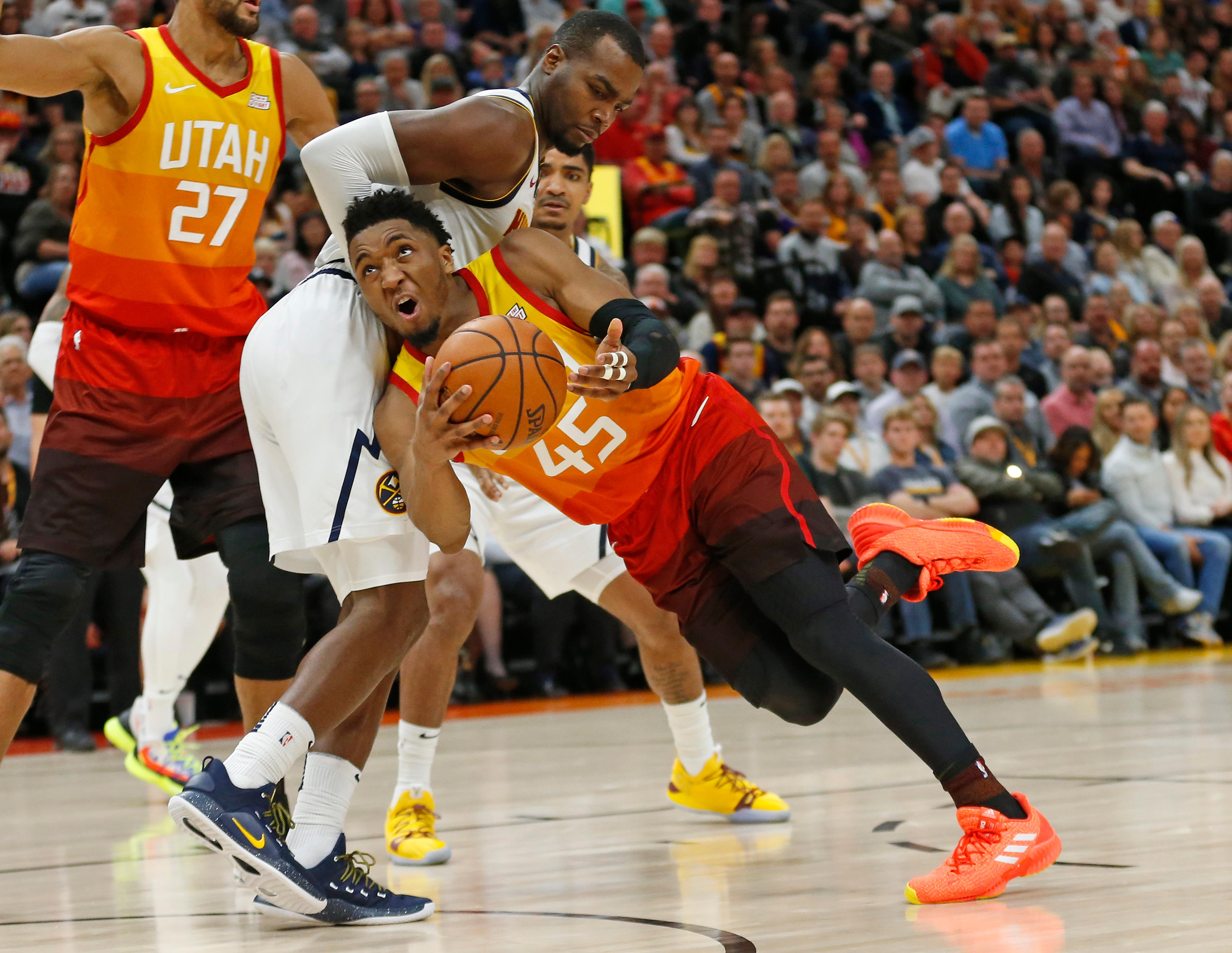 Utah Jazz guard Donovan Mitchell (45) looks to shoot as Denver Nuggets forward Paul Millsap, rear, defends during the second half during an NBA basketball game Tuesday, April 9, 2019, in Salt Lake City. (AP Photo/Rick Bowmer)