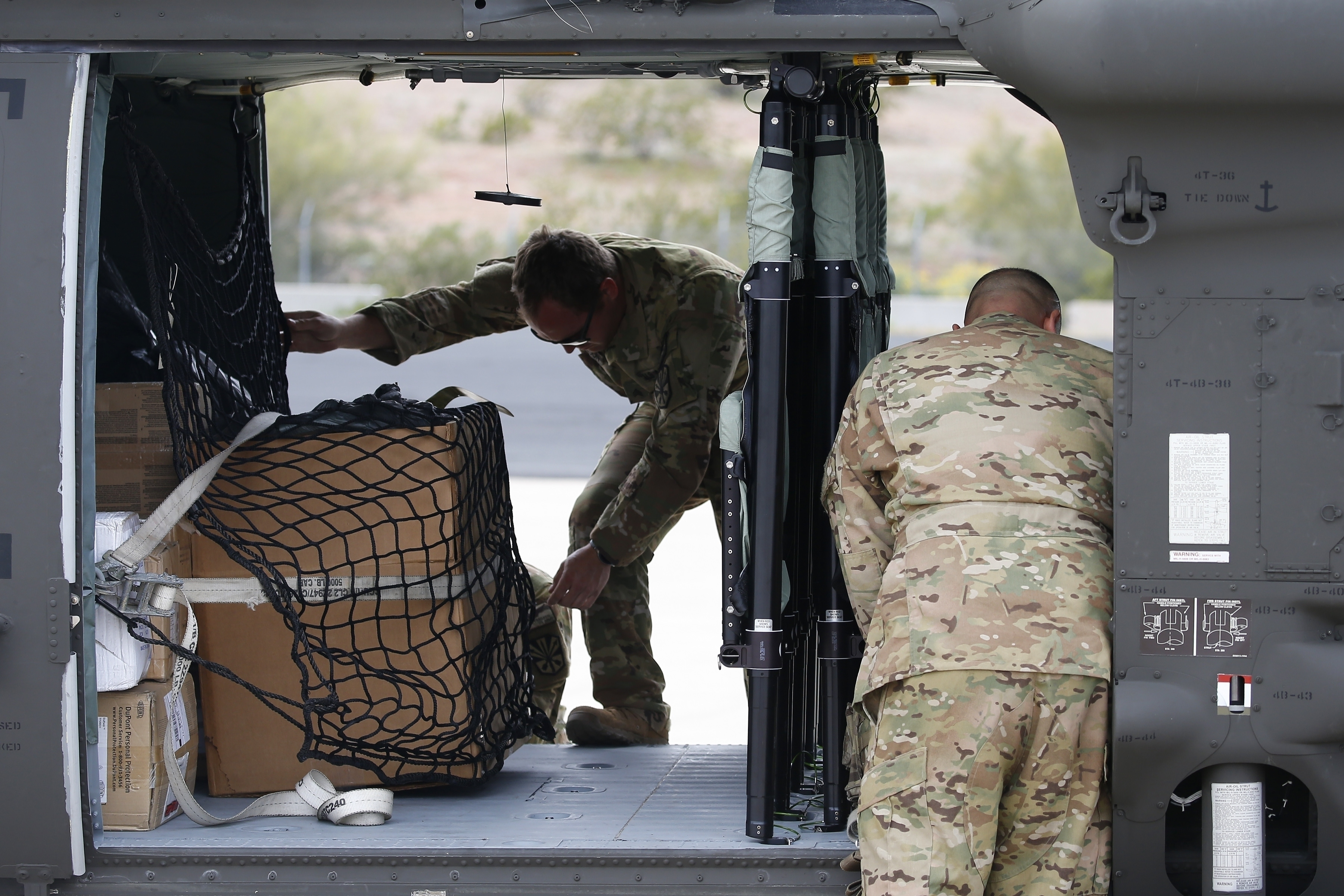 FILE - This March 31, 2020, file photo shows members of an Arizona National Guard unit loading up a Black Hawk helicopter to deliver medical supplies to the remote Navajo Nation town of Kayenta due to the coronavirus in Phoenix. The Navajo Nation has extended its weekend lockdowns preventing people from leaving their homes, except in emergencies, on the vast expanse of land that has been harder hit by the coronavirus than any other Native American reservation in the U.S. (AP Photo/Ross D. Franklin, File)
